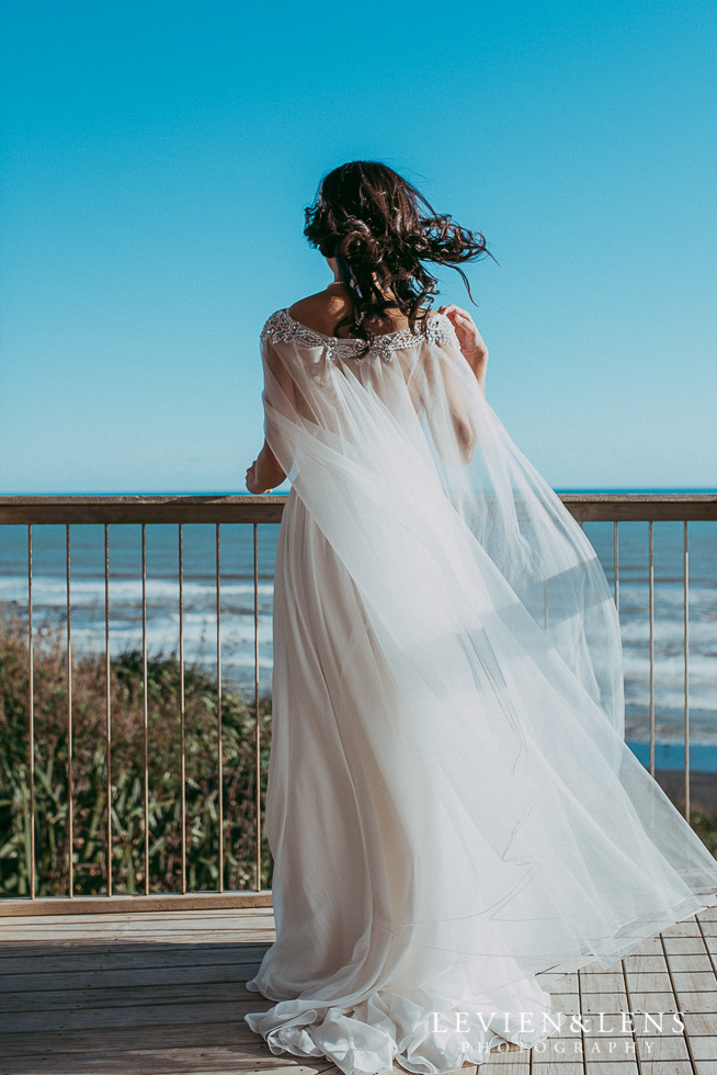 bride standing on balcony {Castaways - Auckland wedding photographers}