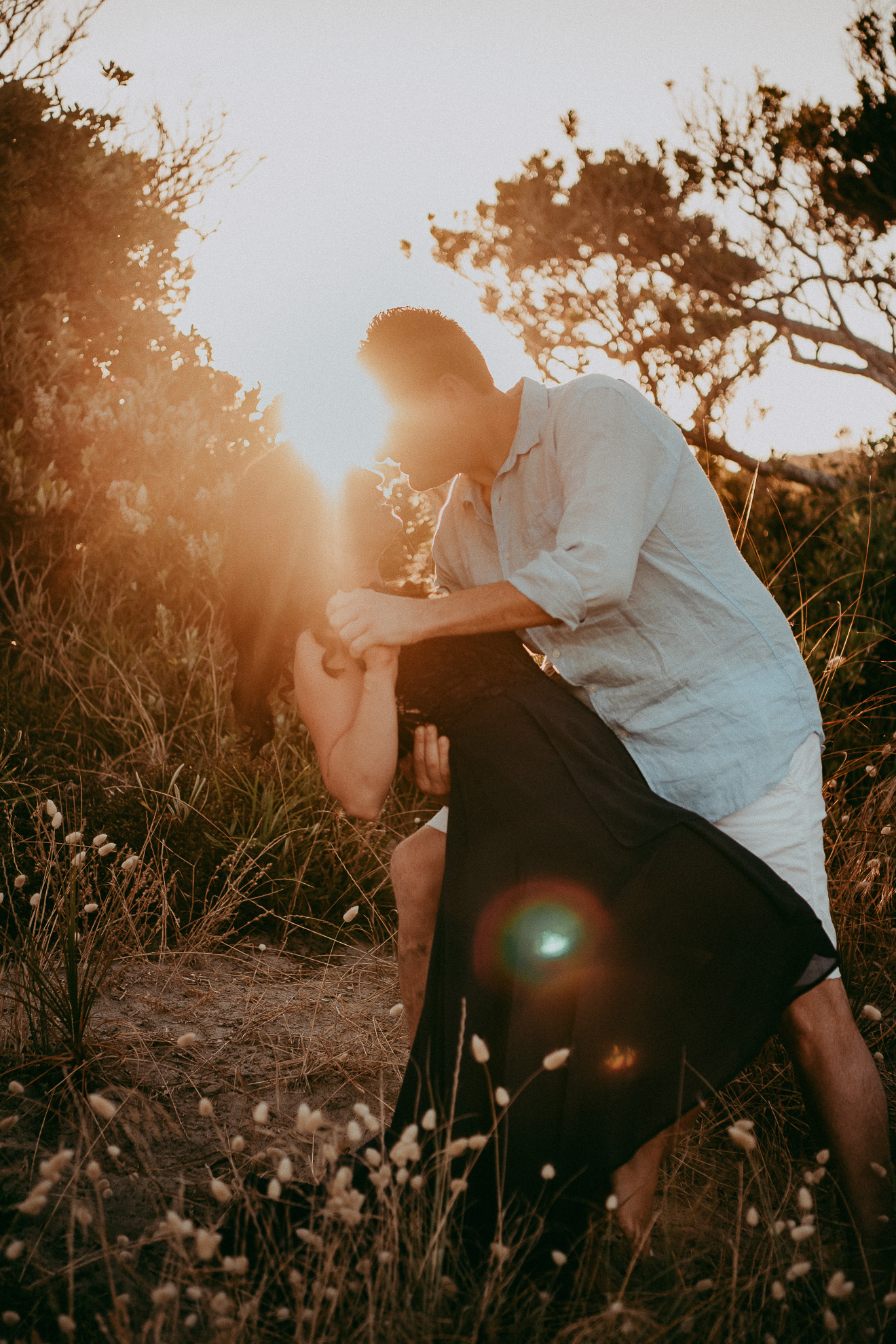 couple engagement pre-wedding hug at sunset beach hills with sun flare | Auckland wedding photographers