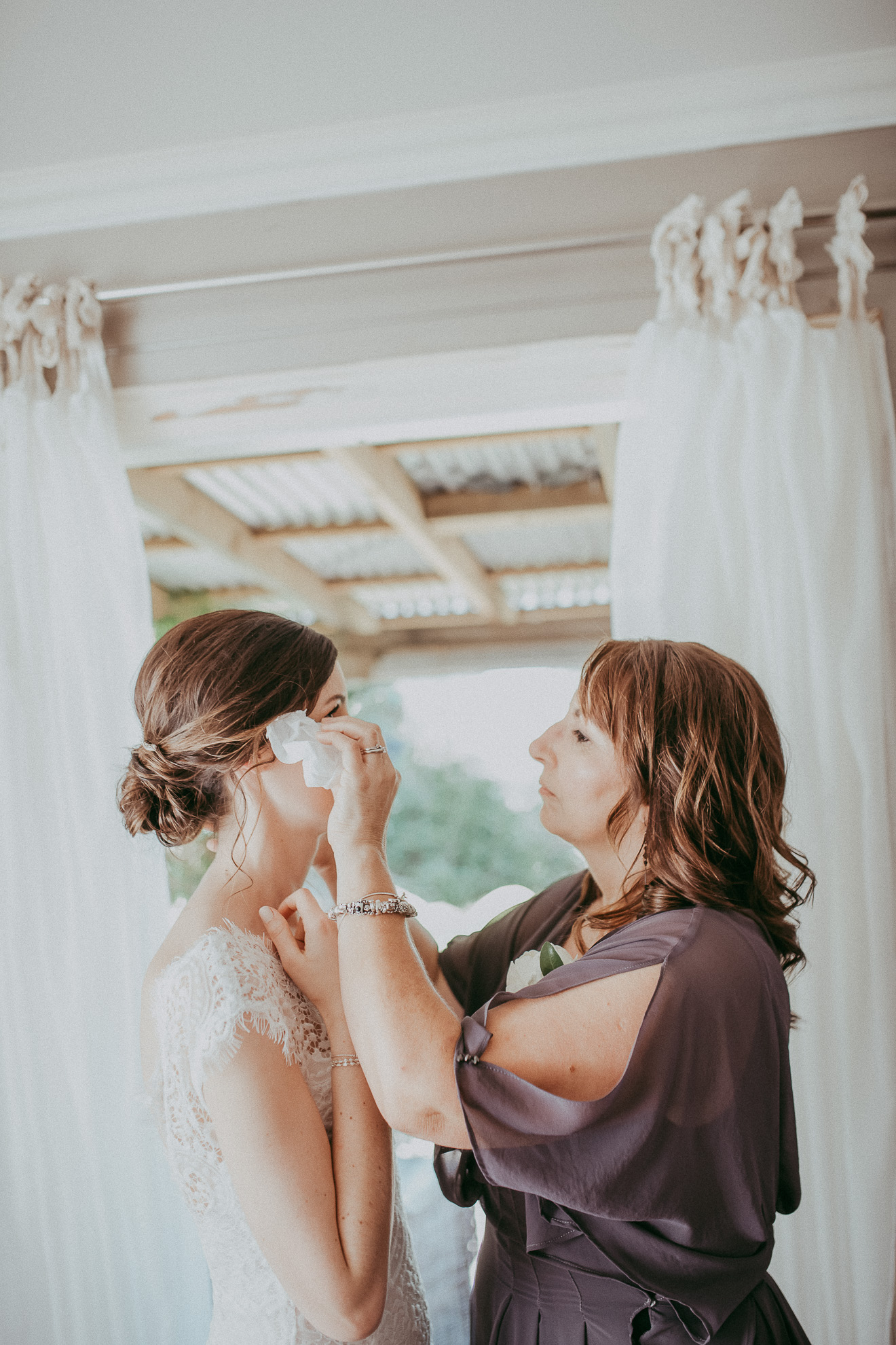 mother of bride wiping tears from brides face at getting ready - Auckland top wedding photographers