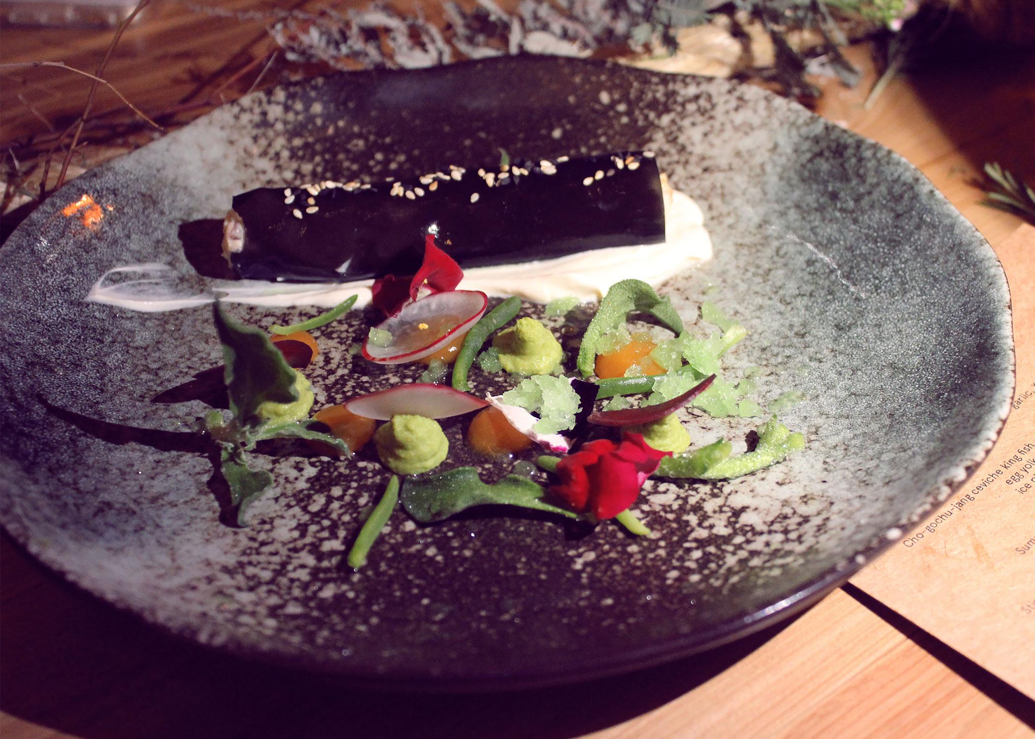 Imitation squid ink cannelloni, prawn & squid filling, wasabi pea puree, smoked yogurt, viola, sesame & yuzu granita