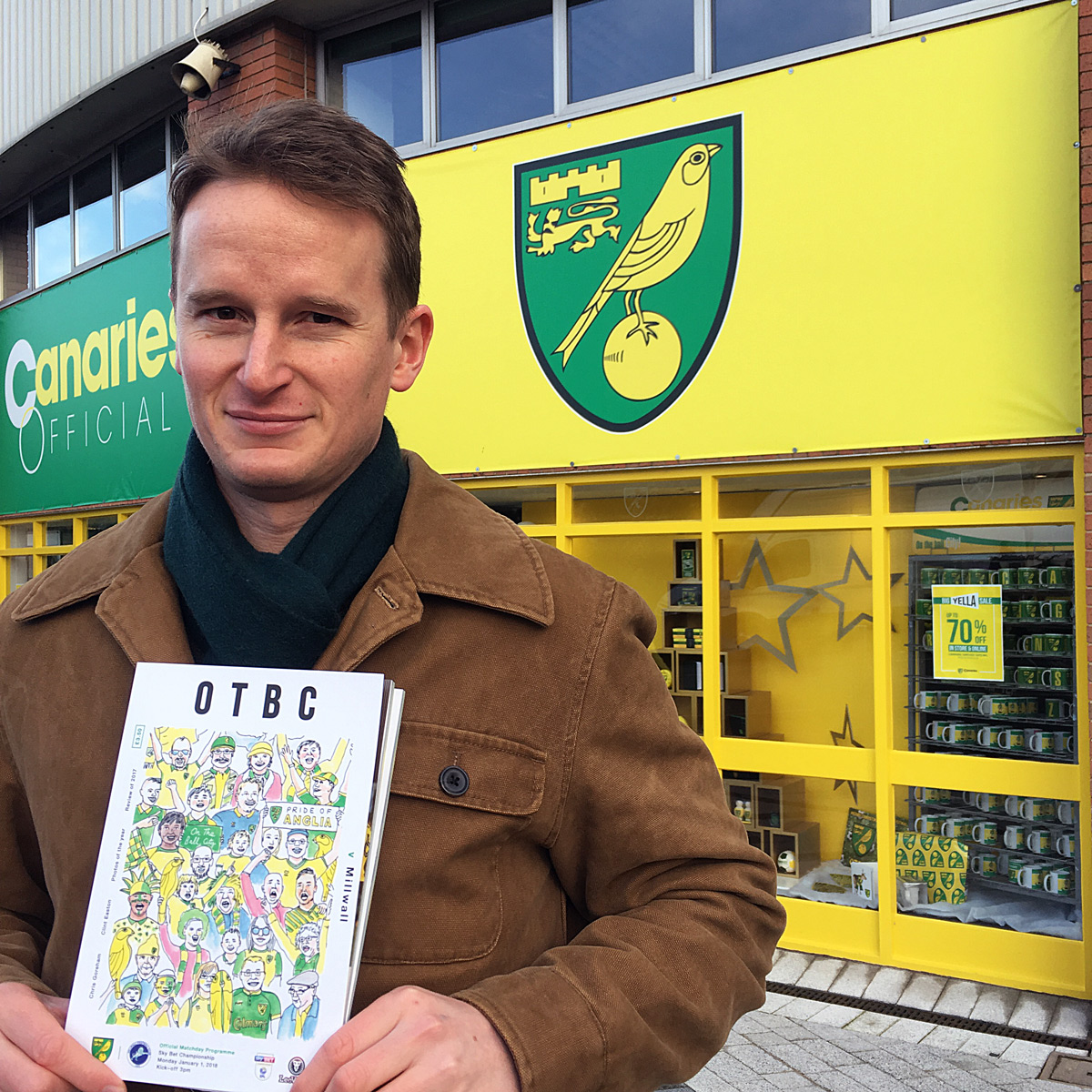 Myself on matchday with the programme featuring my illustration