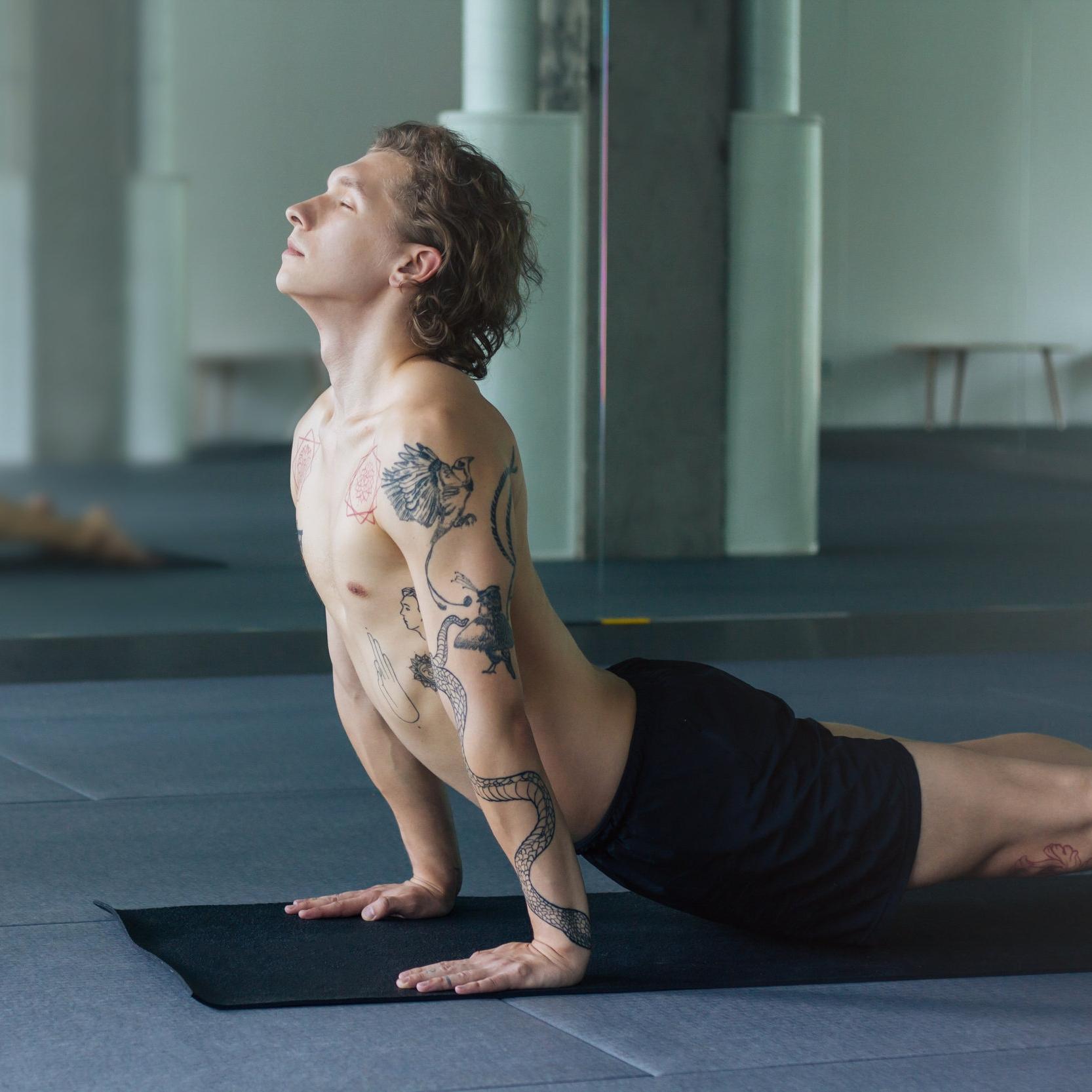 tattooed guy practices yoga