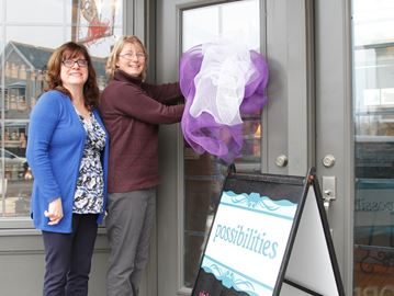 "Local businesses will honour women by placing purple and white bows on their doorfront during International Women's Week here organized by Rev. Janice Chrysler, left. Wendy McCoy, co-owner of ""Possibilities"" is among those businesswomen supporting the event"