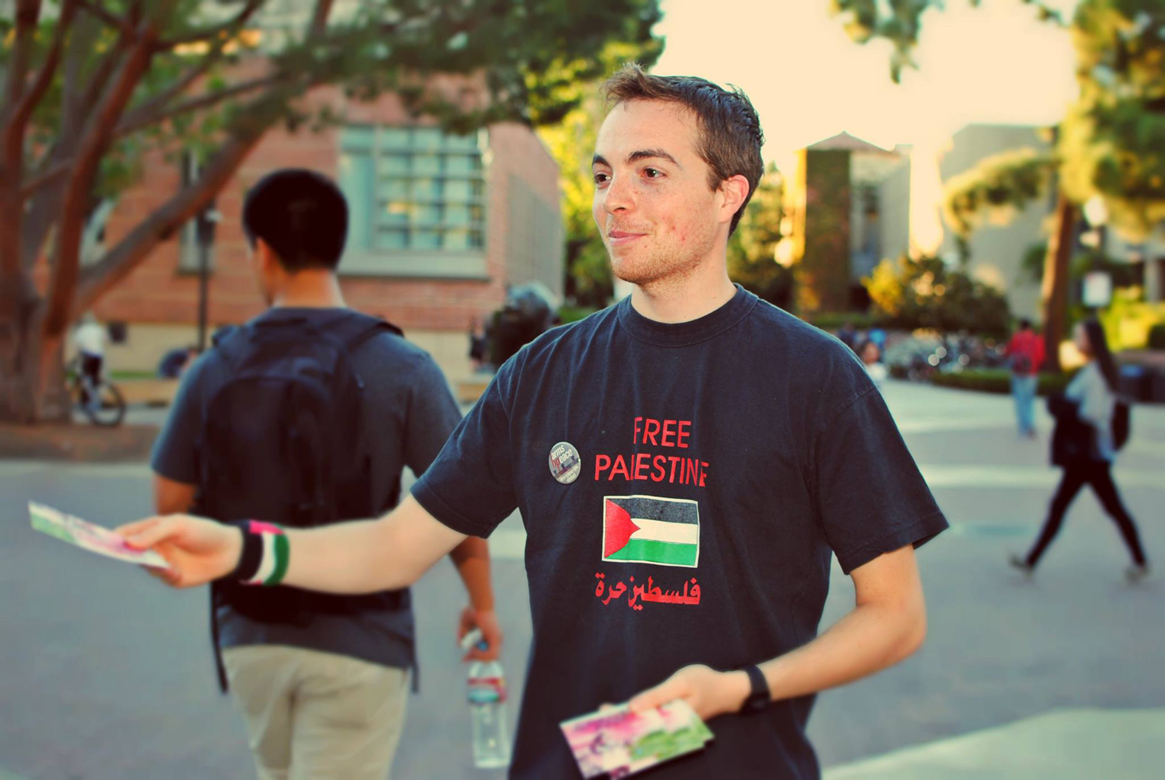 "A student with SJP distributes flyers during ""Palestine Awareness Week"" in November 2014 at the University of California, Los Angeles. (Angélica Becerra)"