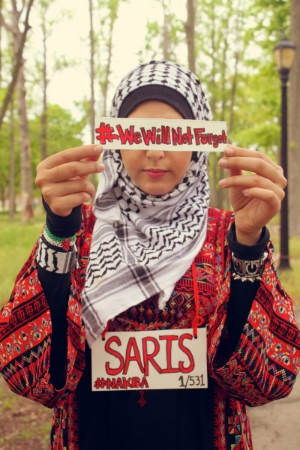 "A student with SJP at the CUNY College of Staten Island wears a sign with the name of a Palestinian village that was depopulated in 1948 as part of the group's ""Nakba Week"" programming. (CUNY College of Staten Island Students for Justice in Palestine)"