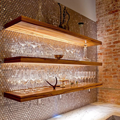 Round metal mosaic creates an alluring atmosphere in a home bar.