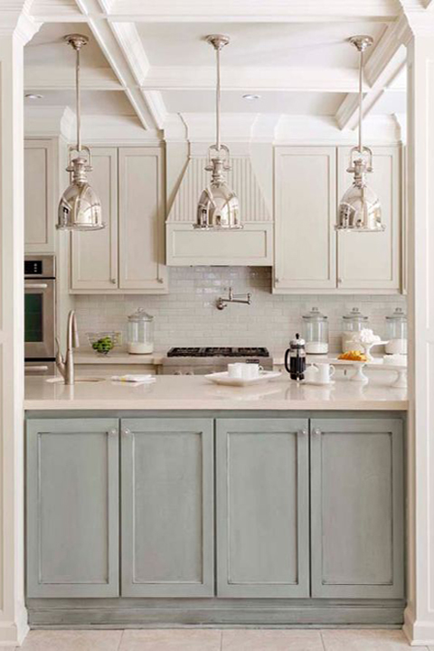 Distressed sage colored cabinets provide a welcome accent in this kitchen by Tobi Fairley Designs.