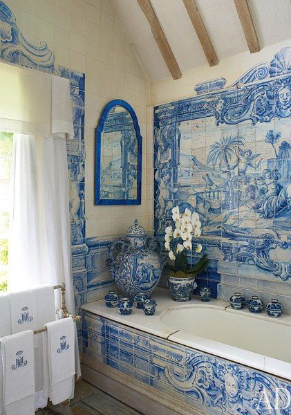 A panel of circa-1730 Dutch scenic tiles decorates the wall above a Victorian tub in the bath of Anouska Hempel's English country estate.