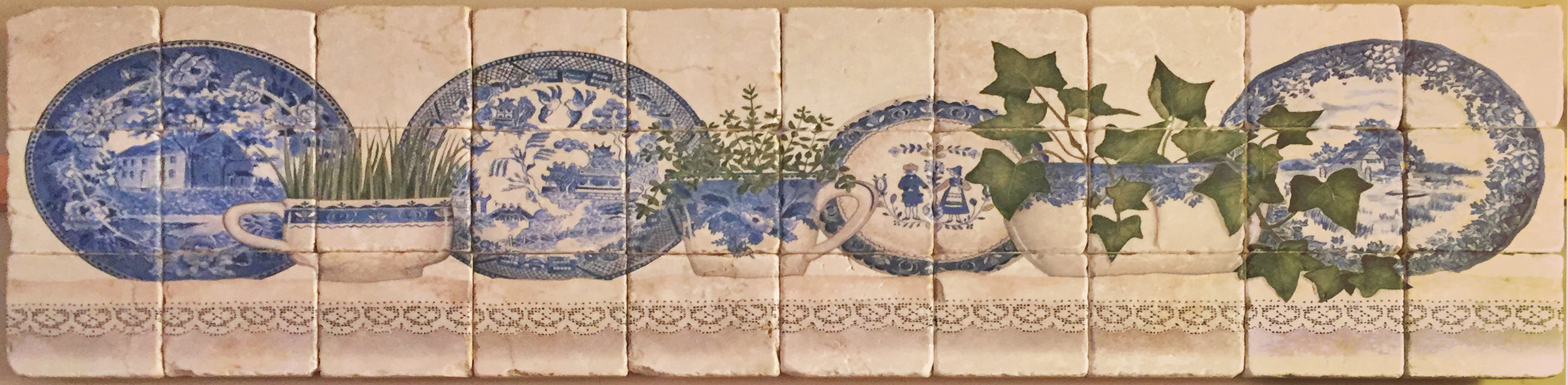 Tile mural depicting blue Delft plates and cups motifs. Available at Statements.