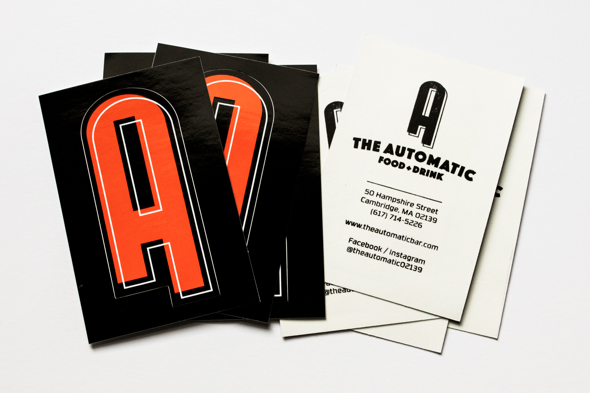 "In lieu of business cards, vinyl stickers with die cut ""A"" on the front and location information printed on the back."