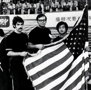 U.S. coach Lee stands proudly behind the American flag with U.S. team member John Simmons (left) and assistant coach, Li Kuo Wang at the 1st World Kuoshu (Kung-Fu) Championships - Republic of China, 1975