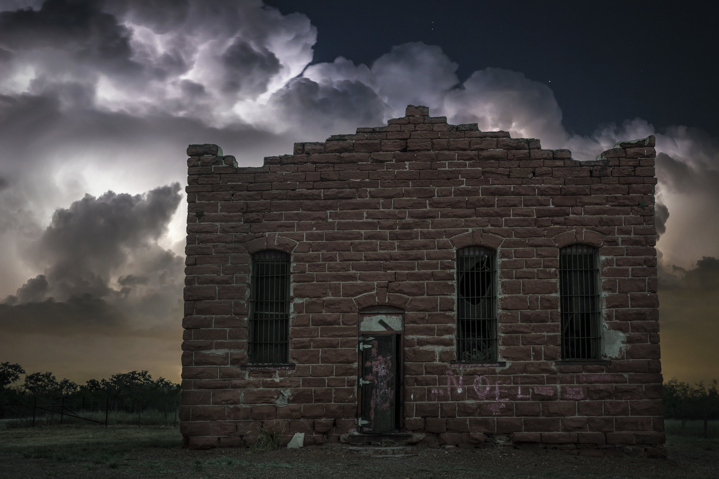 Thunderstorm lights up the sky behind the Old Kent County Jail.