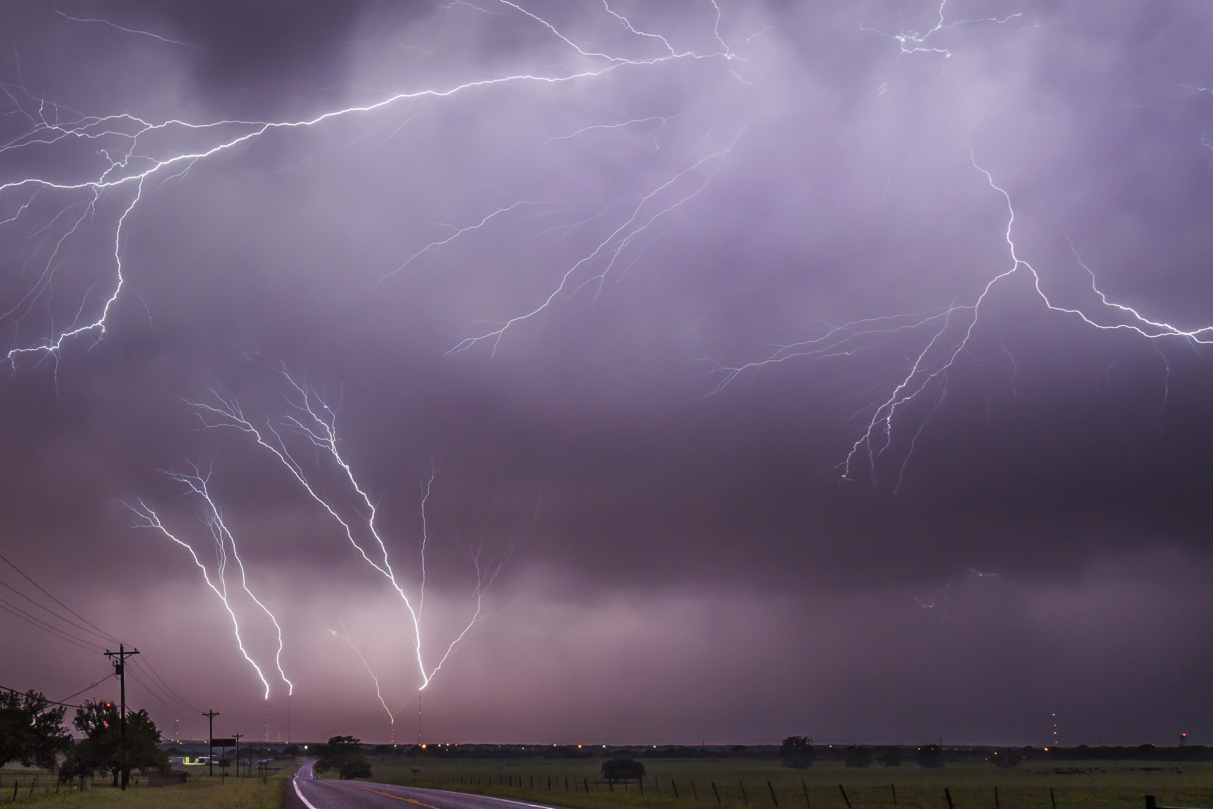 """This is a shot I tried to get for several years. After chasing a disappointing supercell in SW Oklahoma, we were treated to an incredible lightning display on the way home. As we rolled into Bruceville-Eddy, Tx very late that night,the communication towers were initiating """"upward triggered lightning"""" every few minutes."""