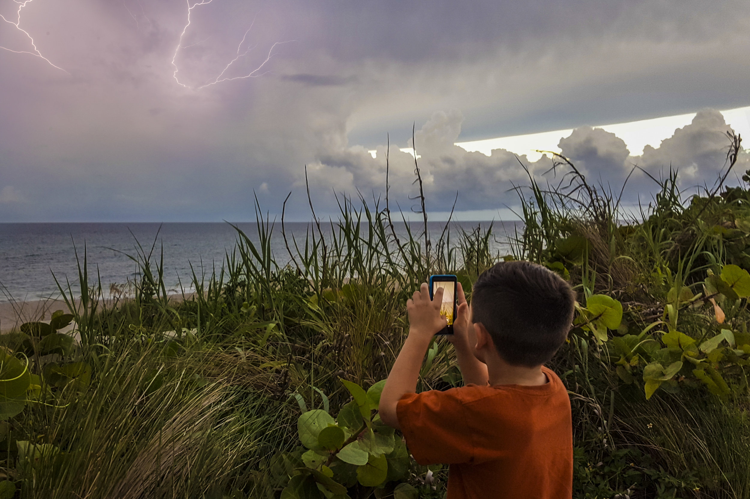 Chase grabbing some video of lightning off the coast of Jupiter, Florida Image by Savannah Weingart
