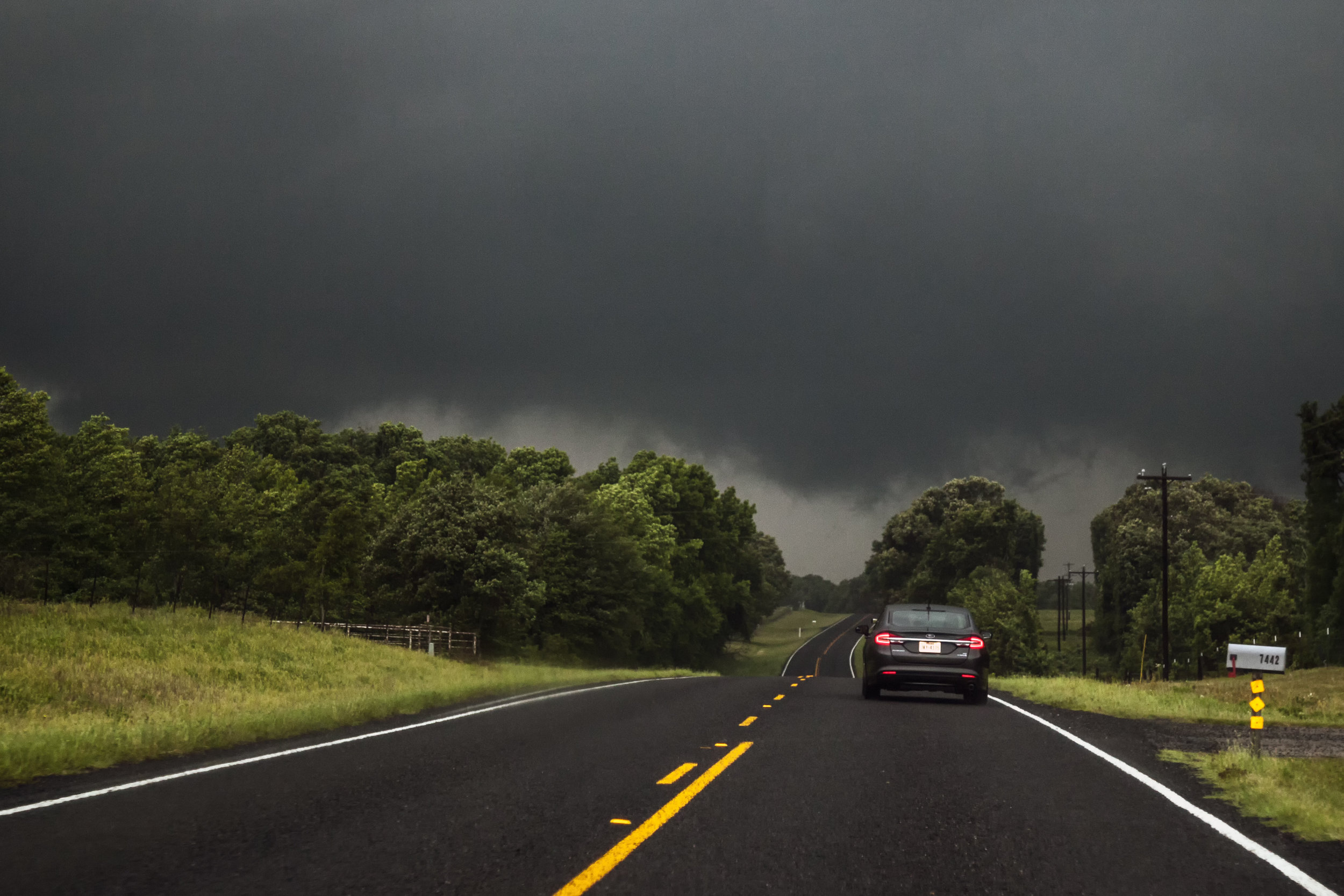 An untrained eye might not notice the violent tornado just behind the trees on the left. Chasing in East Texas is incredibly difficult due to the thick trees and plentiful hills.