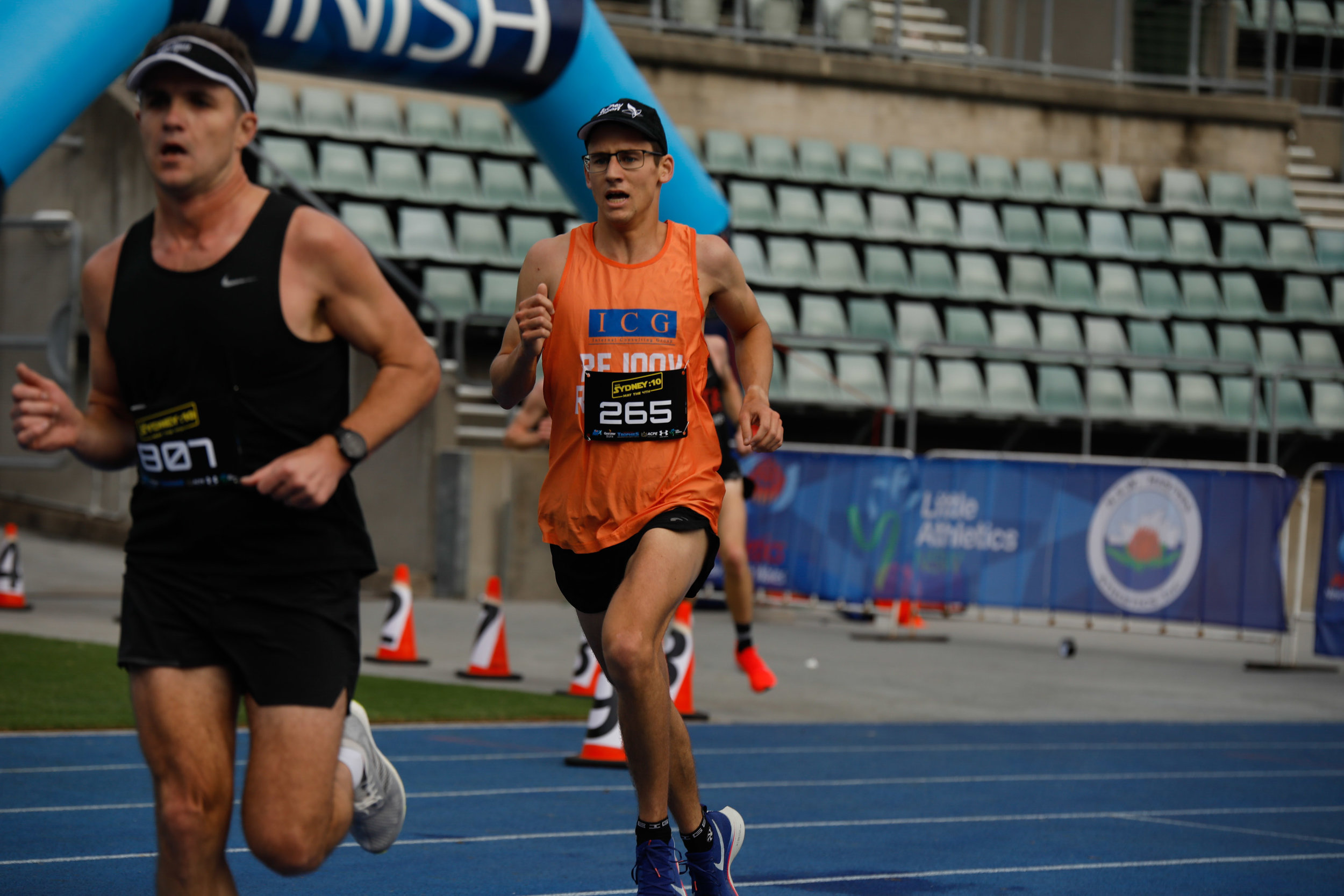 33:44 PB Sydney 10k 4/5/19 Dom Bullock coming onto the track sprint finish off of the road course, about to overtake Brendan Fehon in black