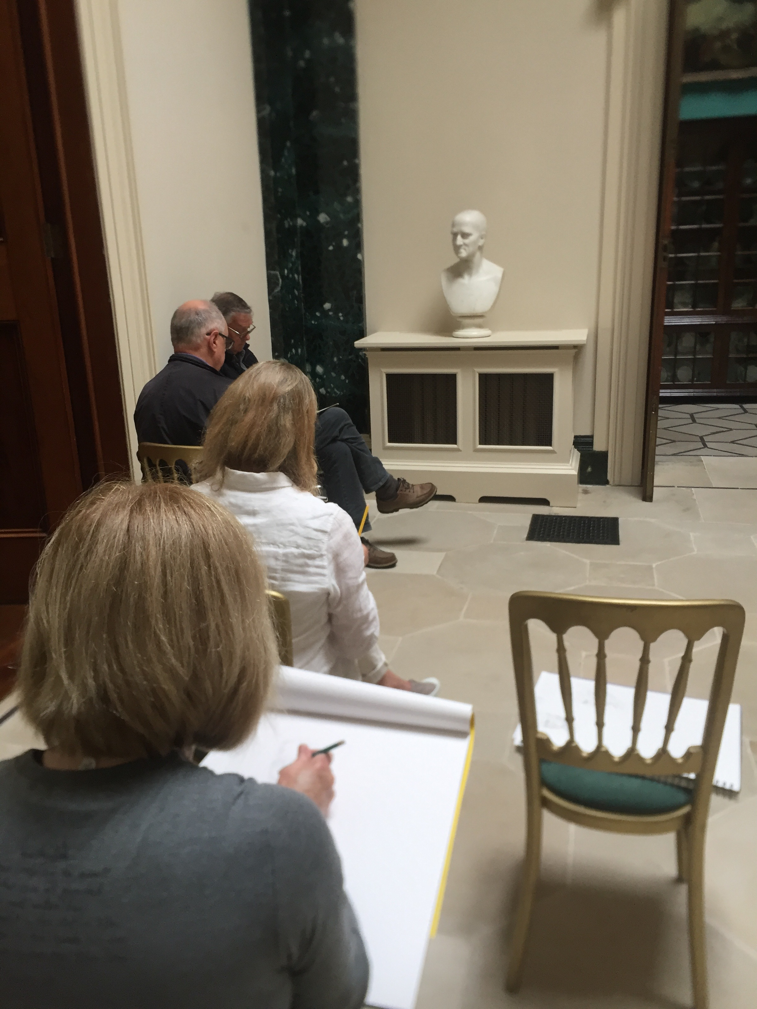 Students drawing one of the busts.