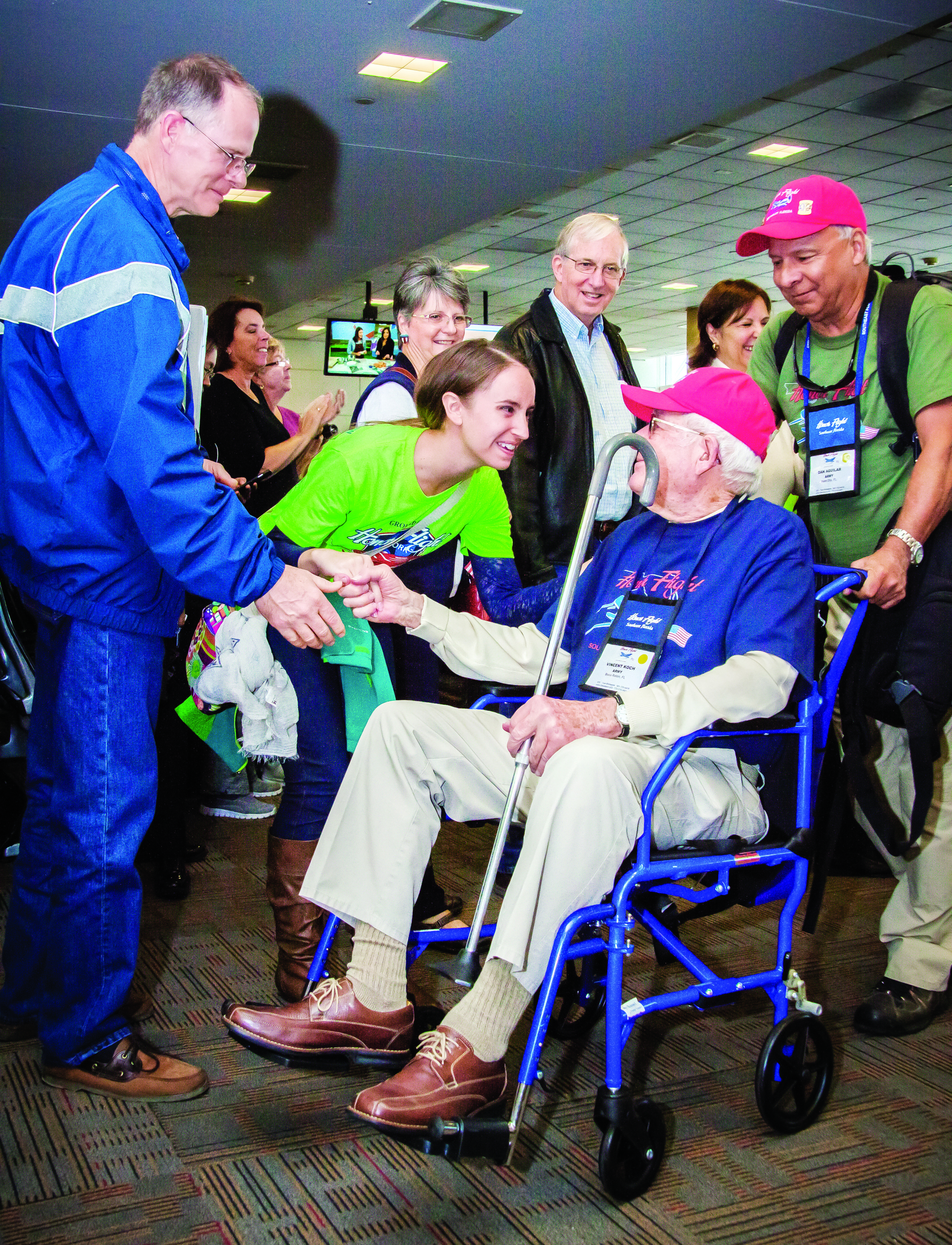 World War II Army veteran Vincent Koch is pushed by his guardian, Army veteran Dan Aguilar, Palm City, as he shakes hands with an enthusiastic member of the Honor Flight Ground Crew and greeted by others during his arrival in Washington, D.C., Oct. 24 on the Southeast Florida Honor Flight.