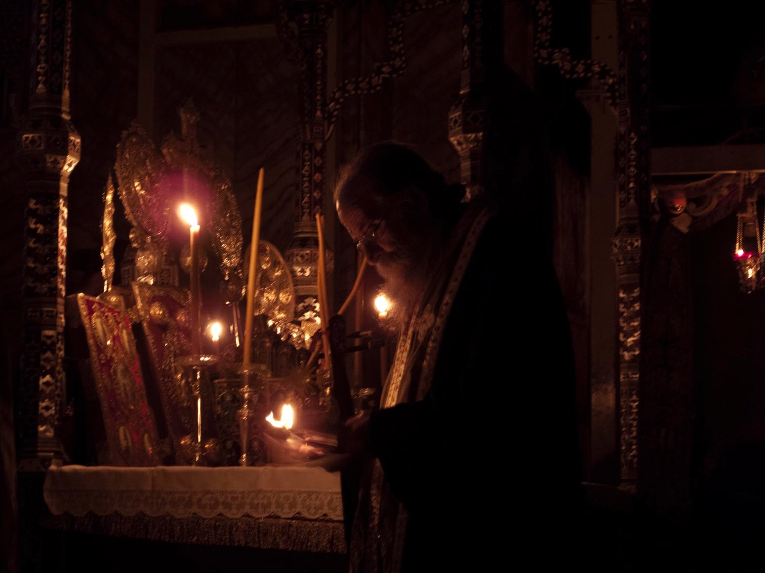 At the holy altar on the Feast of the Saint, Father Pavlos borrows the glow of a few tapers to read names of those who have sought his prayers.