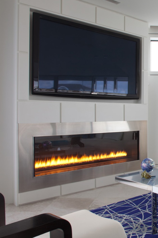 Modern stainless steel electric fireplace with mounted TV and great accent pieces