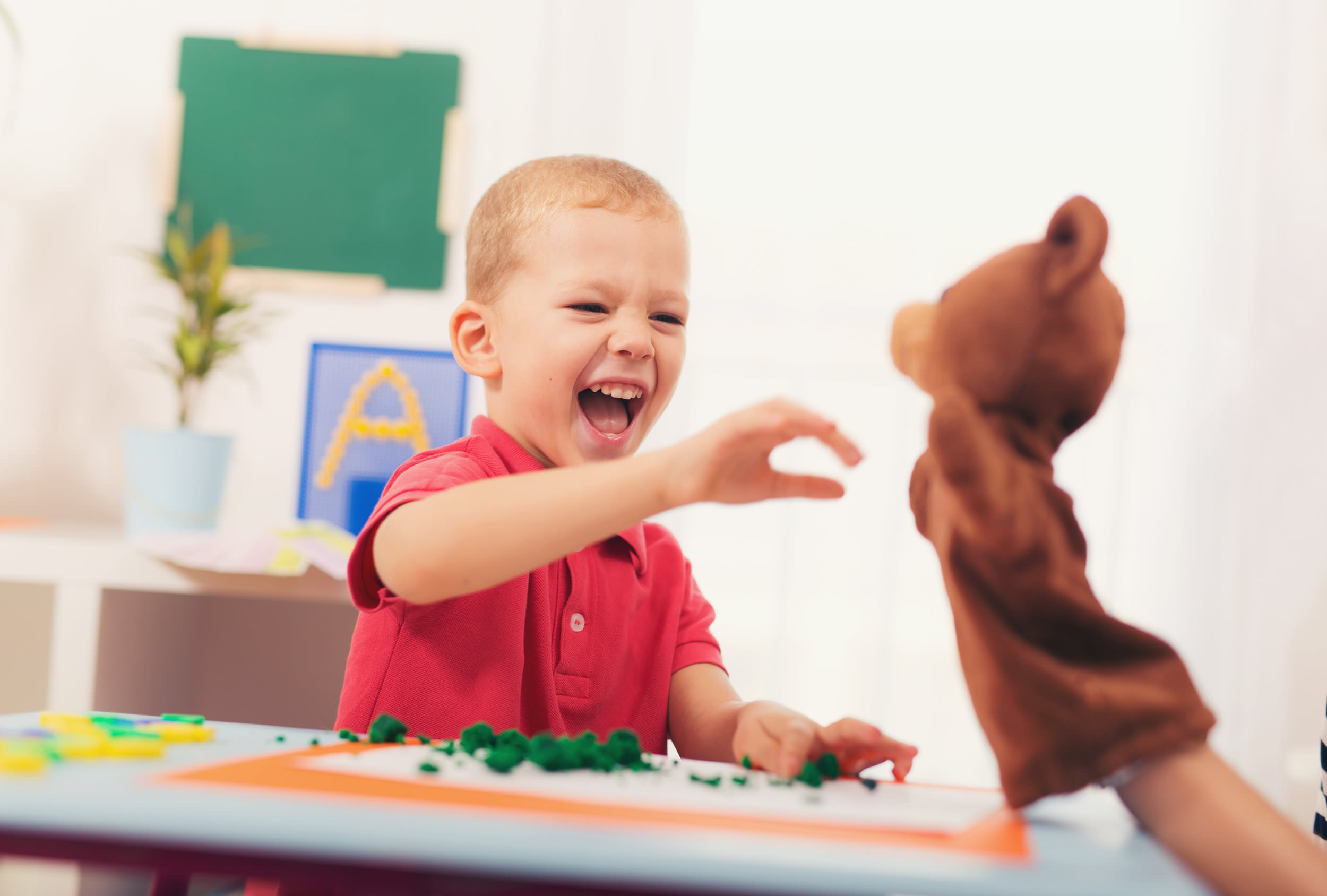 boy laughing while interacting with toy bear.jpg