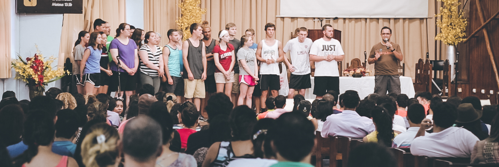 Team members crowd together as Pastor Djard introduces them to the Brazilian students.