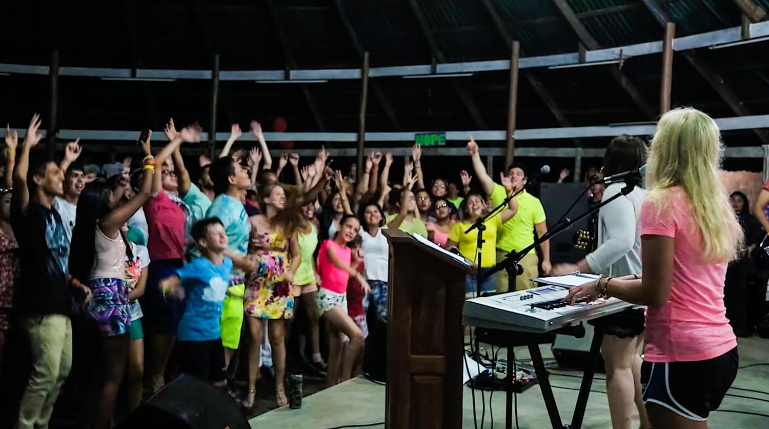 Students worship energetically during a nighttime chapel session