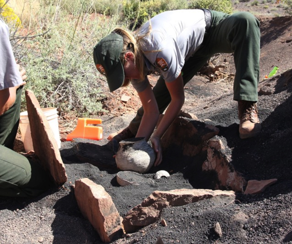 NPS Archaeologist Removing a Ceramic Jar from the Disassembled Cist