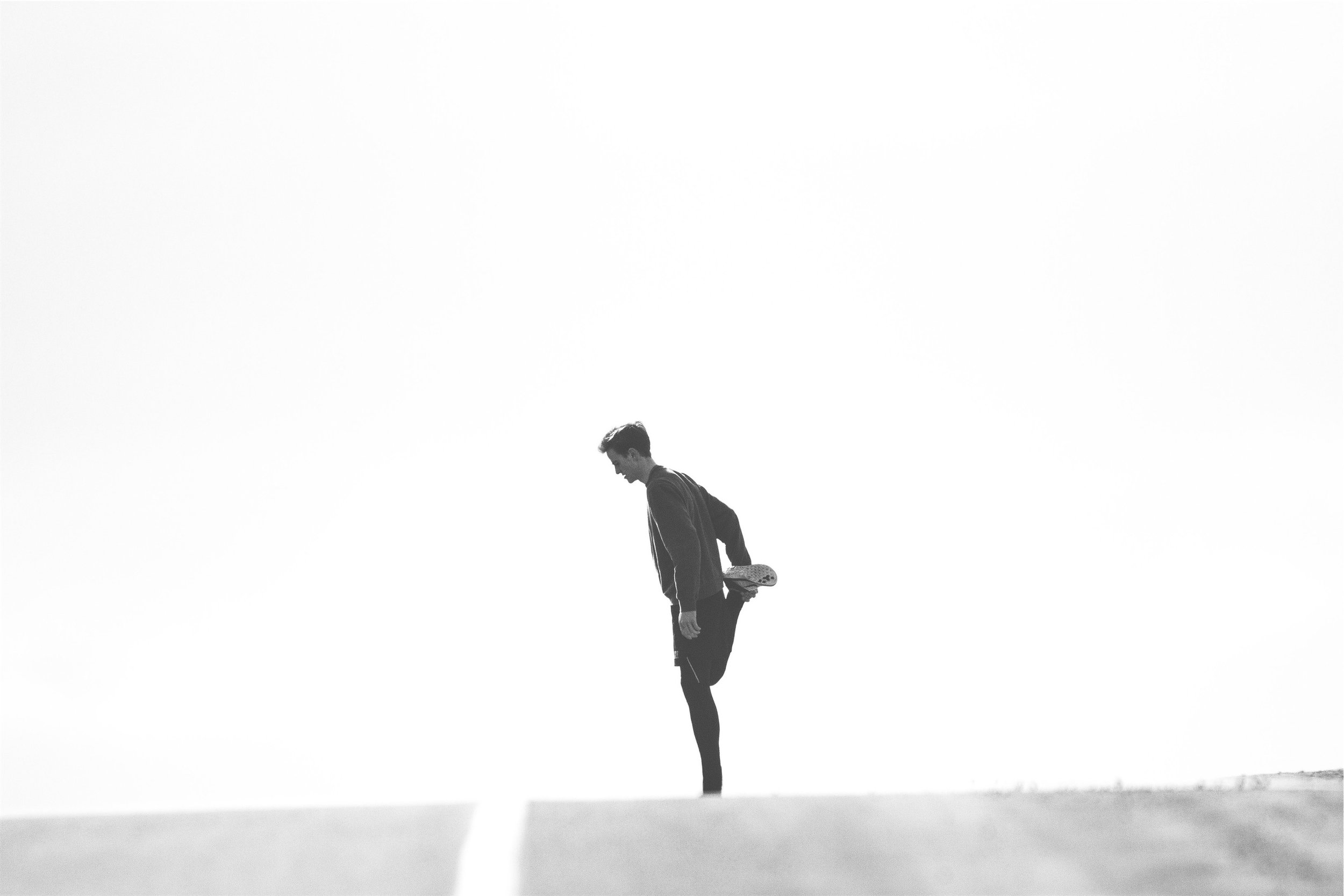 Man stretching on road prior to running