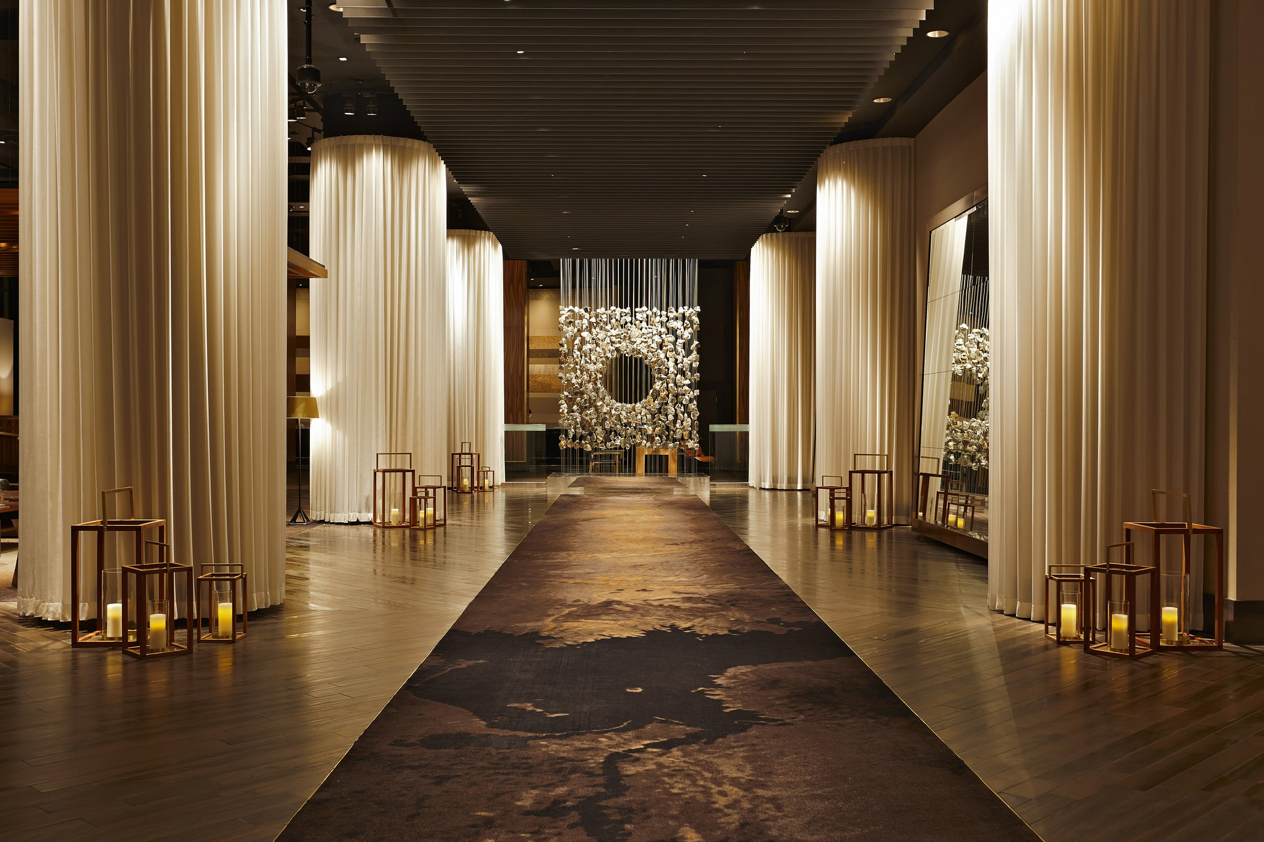The lobby is lined with structural columns that are hidden behind sheer drapery, making this space feel warm and cozy. These sheer drapes also give the space that little touch of sexiness, reminding you of bed sheets.
