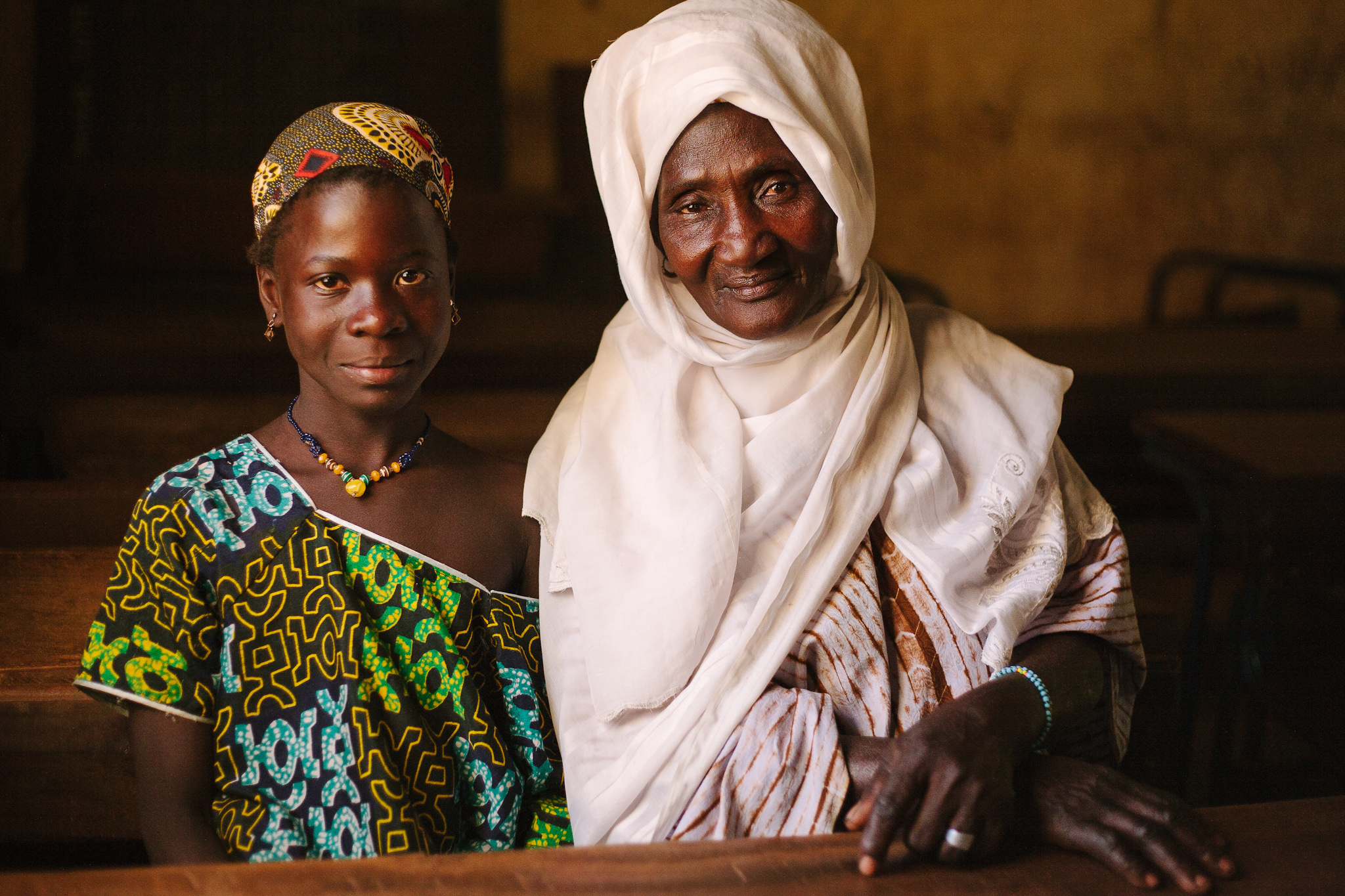 Kadjatou Bagayogo sits with her grandmother, Sira Samake, in a Beneko classroom. Kadjatou is a classmate of Moussa's, and is interested in going into teaching when she grows up.