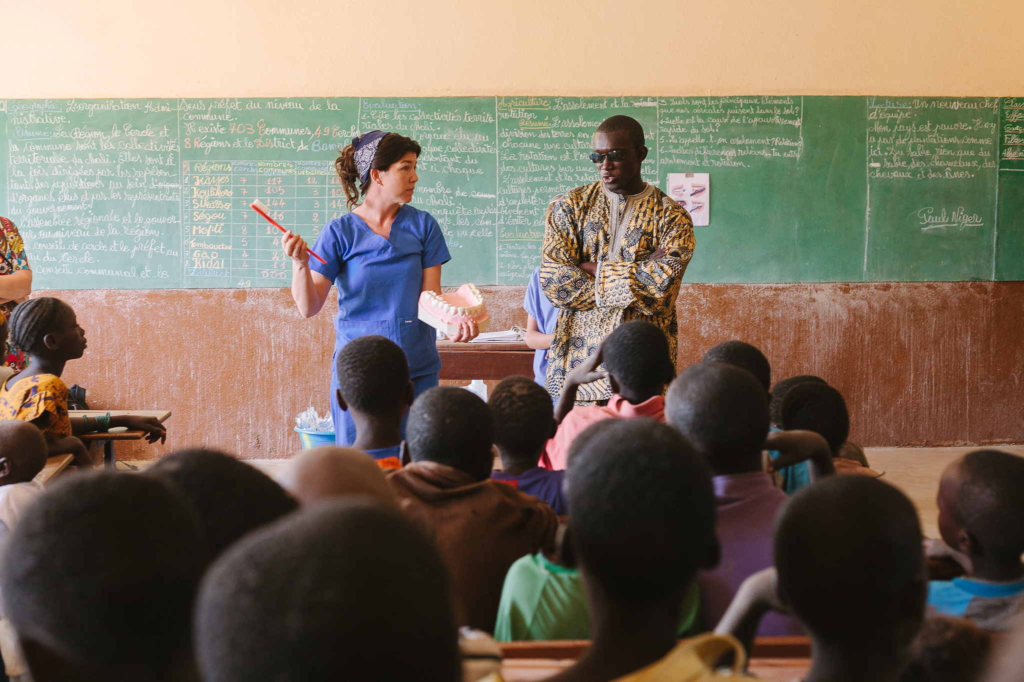 Inside a schoolroom in Gnekekoro, a volunteer health educator teams up with a translator to host a brief session on dental health and hygiene. Gnekekoro worked with Mali Rising in 2009 to construct a middle school, which now enrolls 90 students.