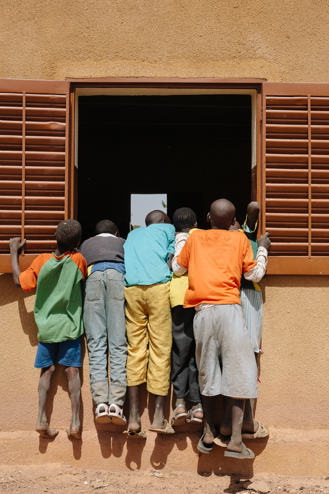 In the village of Gnenkekoro, children hang from a school windowsill in order to observe the dental clinic taking place inside.