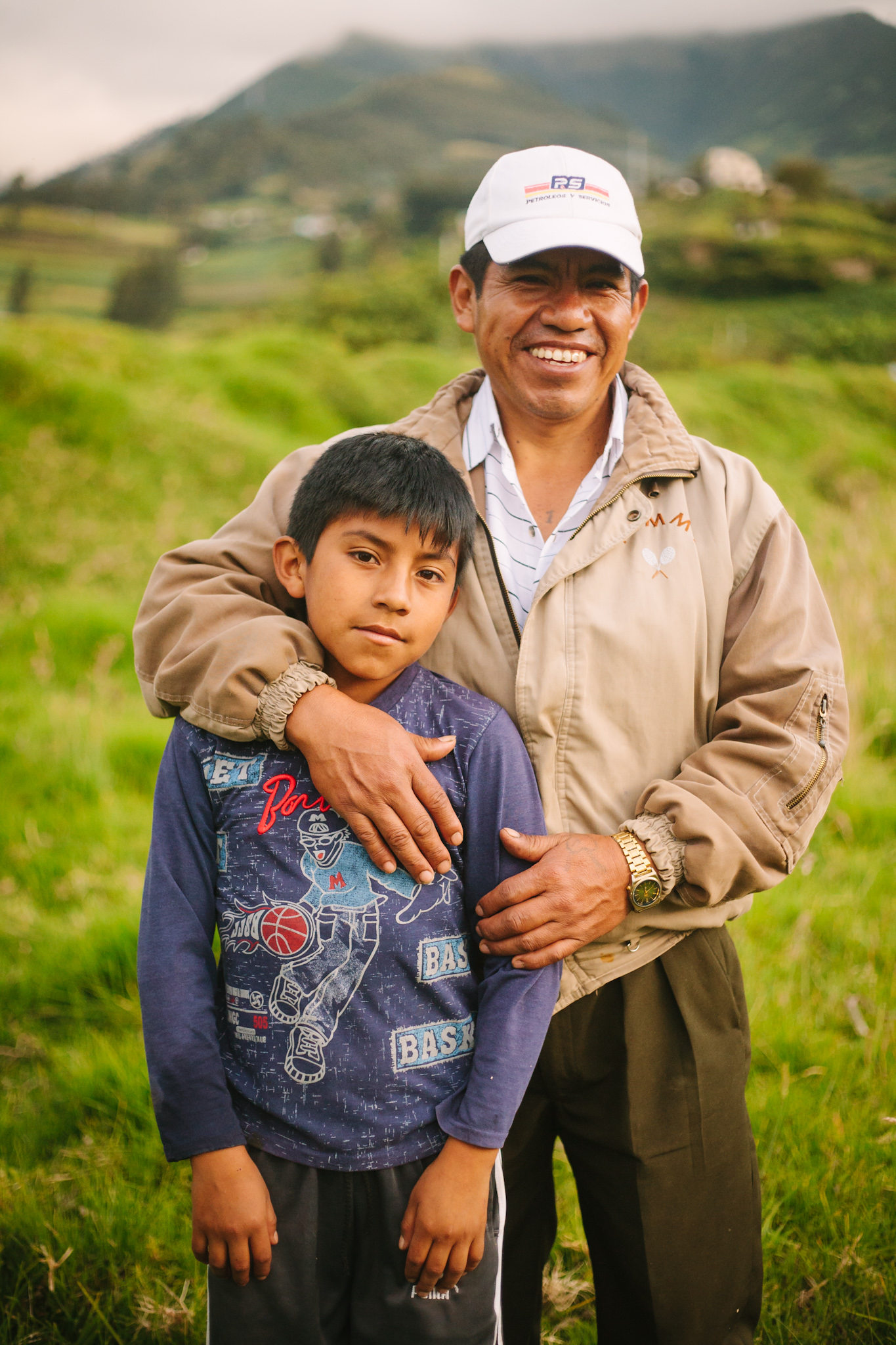 A father and son stand on the sidelines of a soccer match in Pij  ál, an Andean village in Ecuador that operates its own homestay program for international travelers.