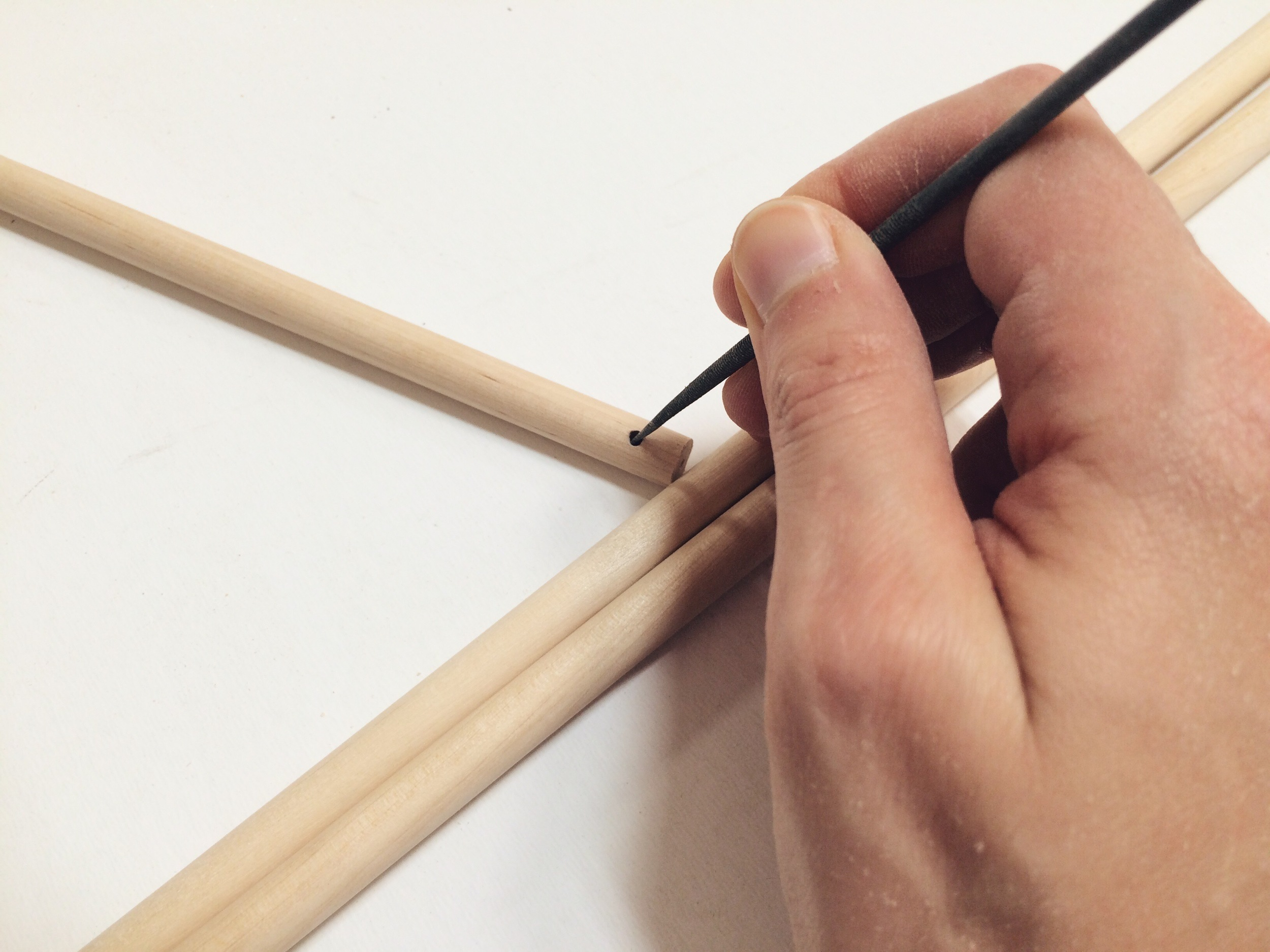 Holes are drilled in the end of the rod, hiding the knot at the end of the string.