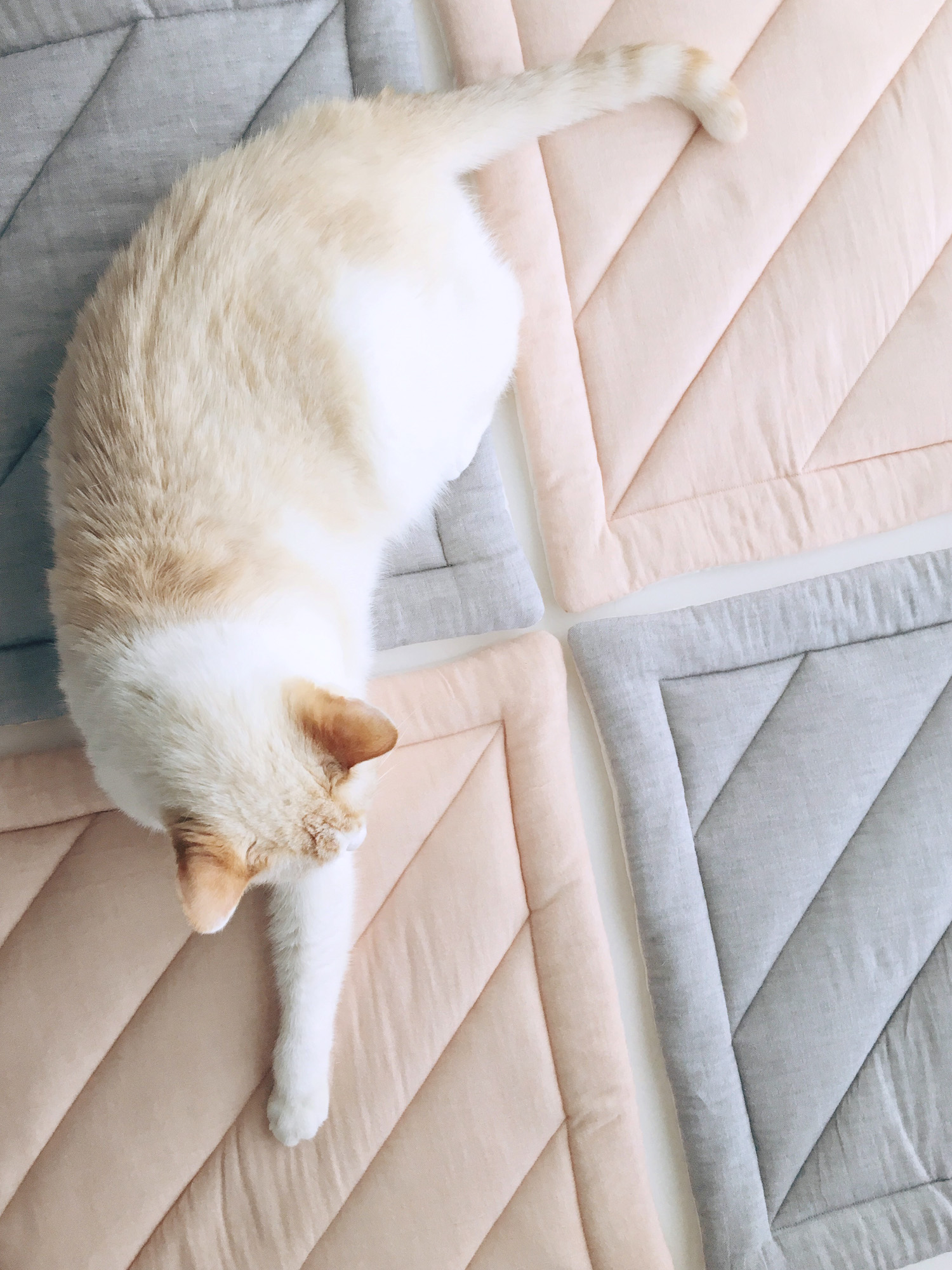 quilted cat mats in cherry blossom and pebble grey