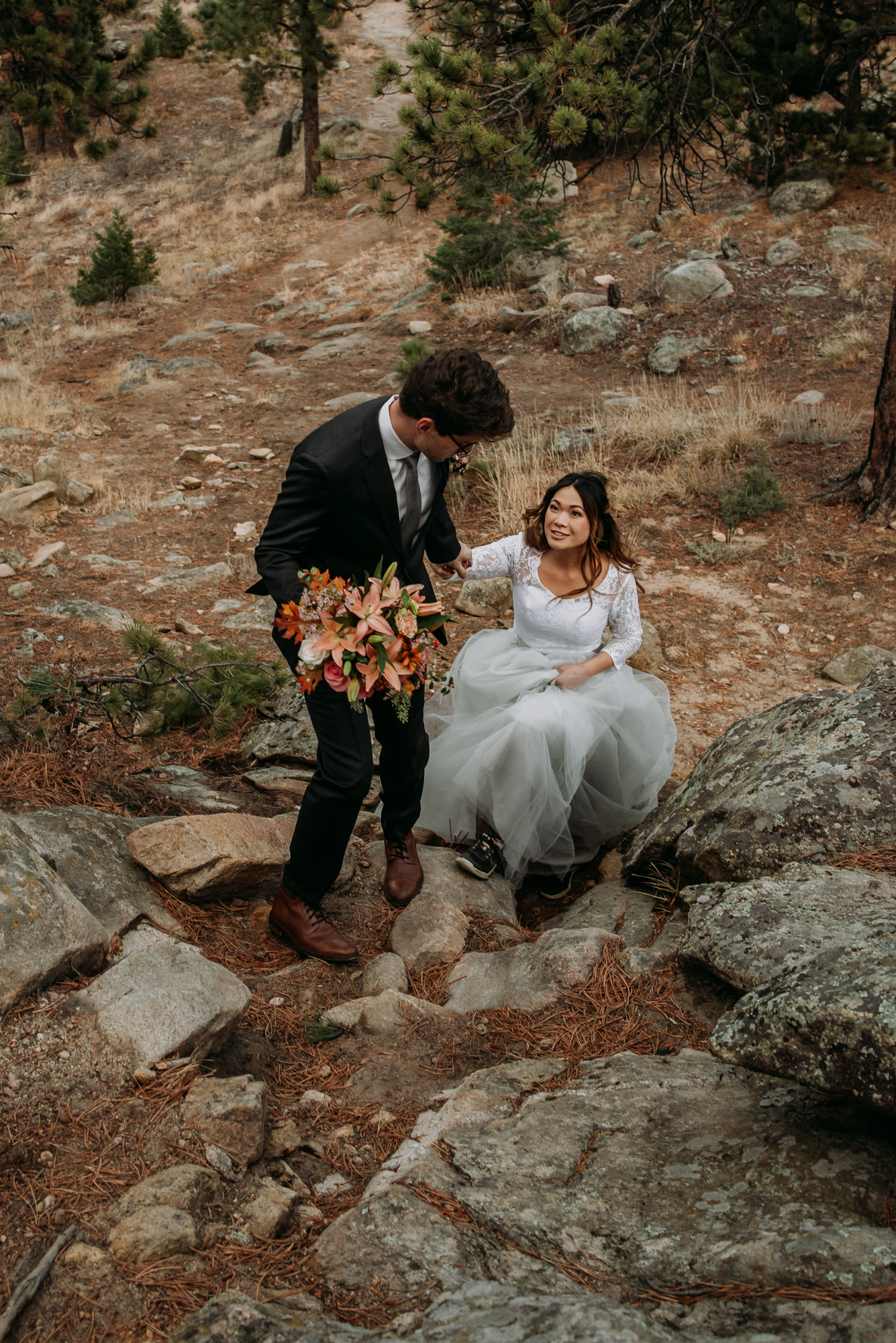 Justin helps Alice climb up the rocks in her wedding dress.