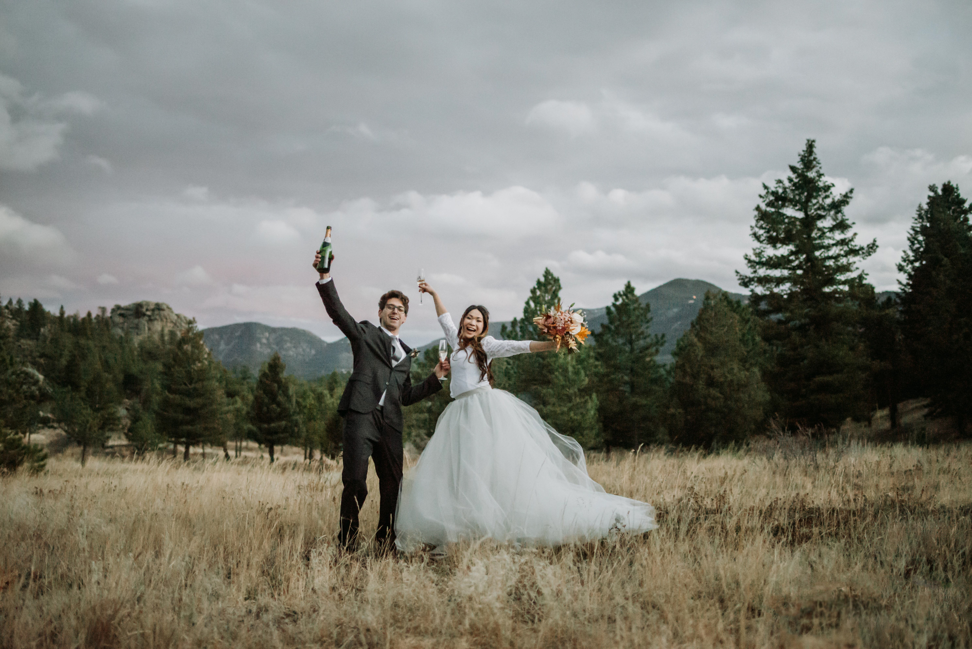 A couple jumps for joy at their boho mountain elopement in Colorado.