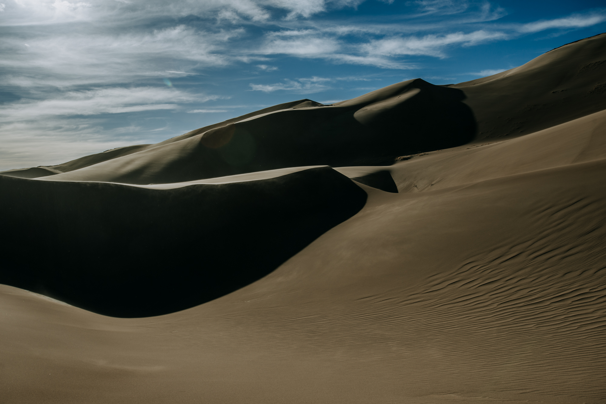 The shadows and harsh afternoon sun create abstract shapes at Great Sand Dunes National Park.