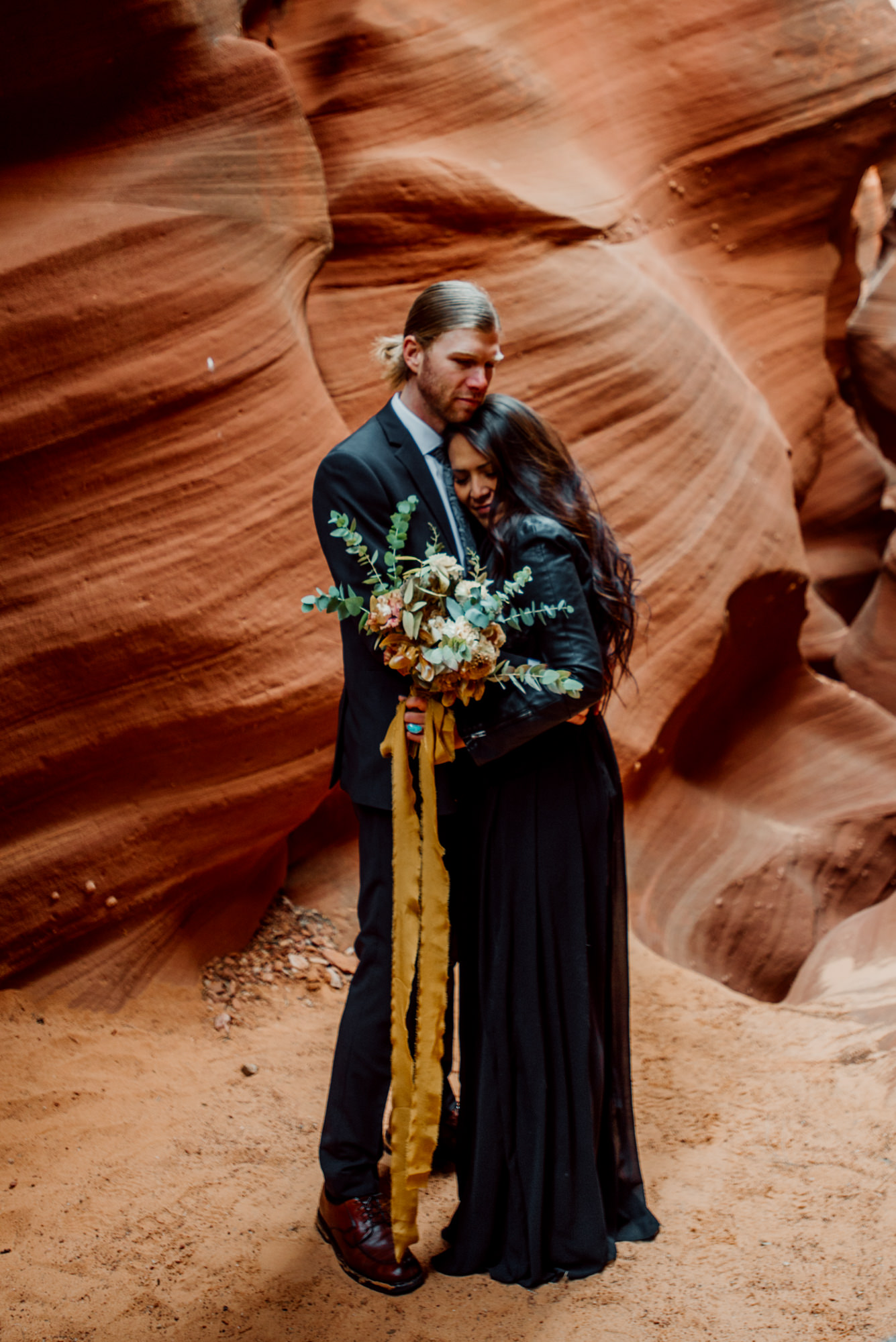 A gorgeous desert wedding featuring a bouquet with a yellow ribbon.
