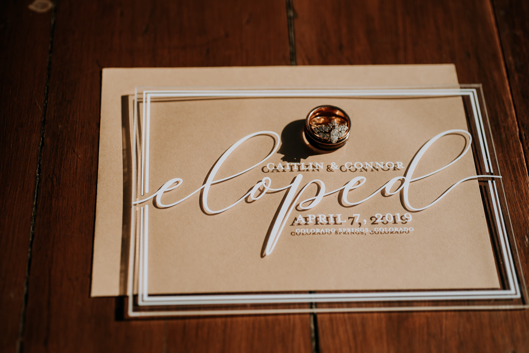 An elopement announcement in white script on a clear surface.