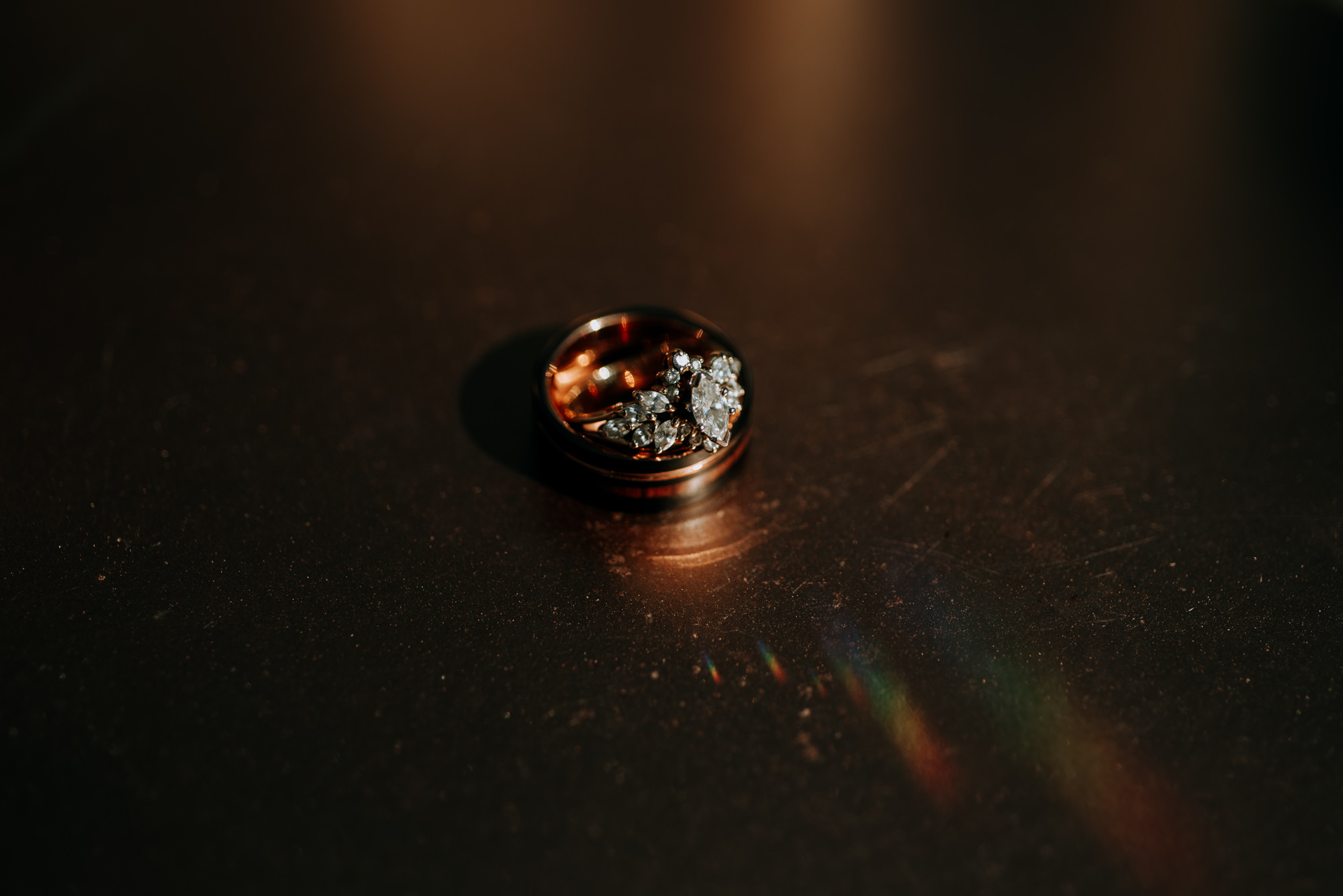 A rose gold and diamond wedding ring is placed on top of his wedding band. Rainbow refracts on the rose gold surface.