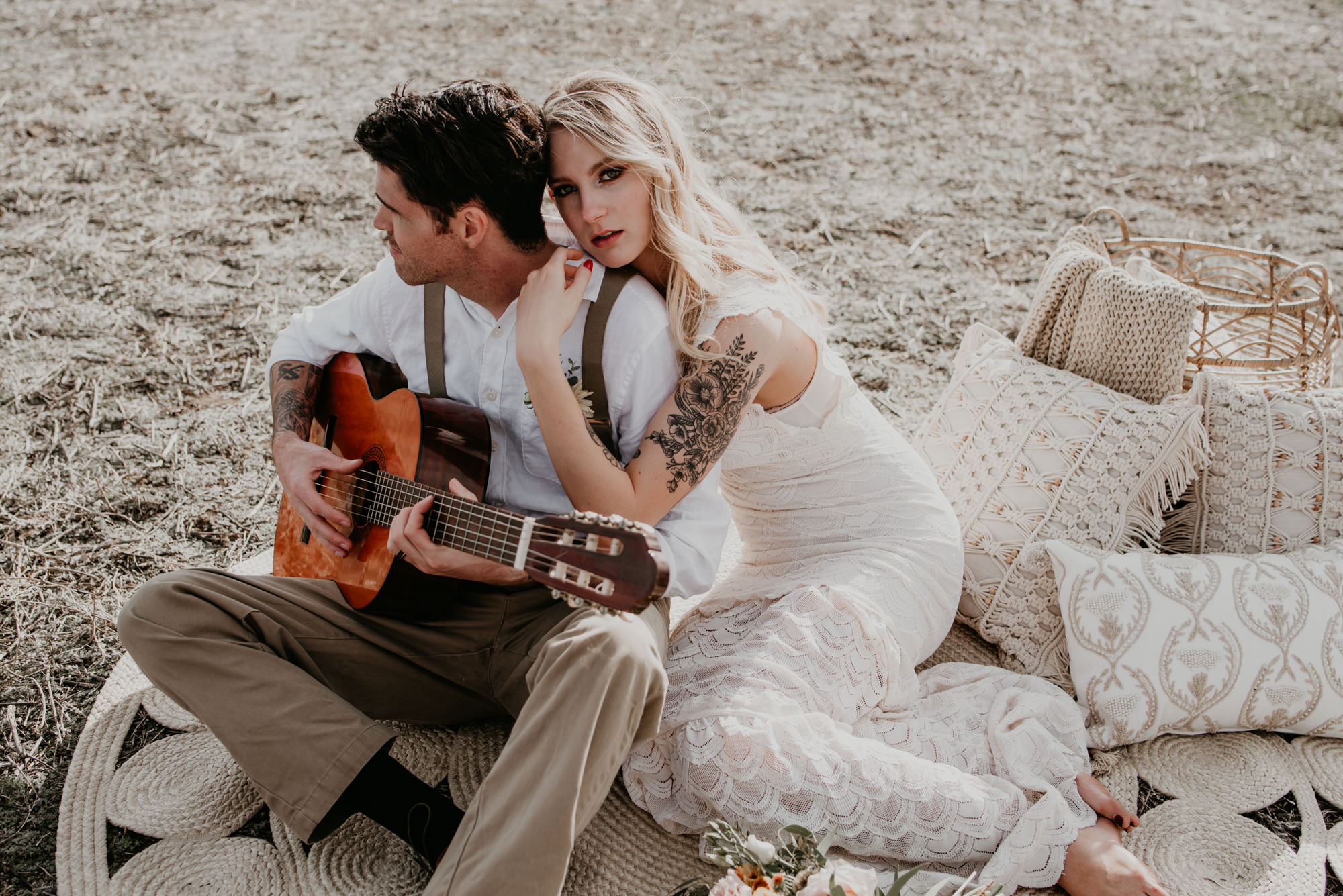 The bride looks at the camera while her husband plays guitar.