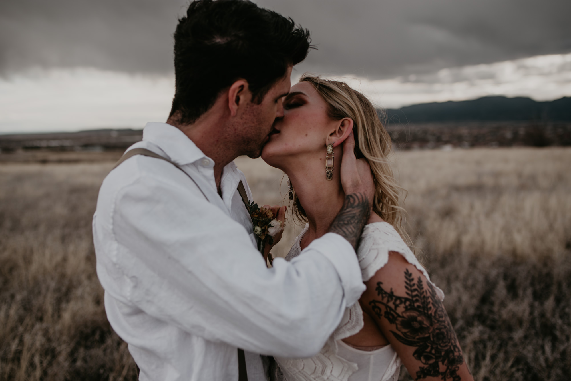Bride and groom share a romantic kiss under dark grey and moody skies.