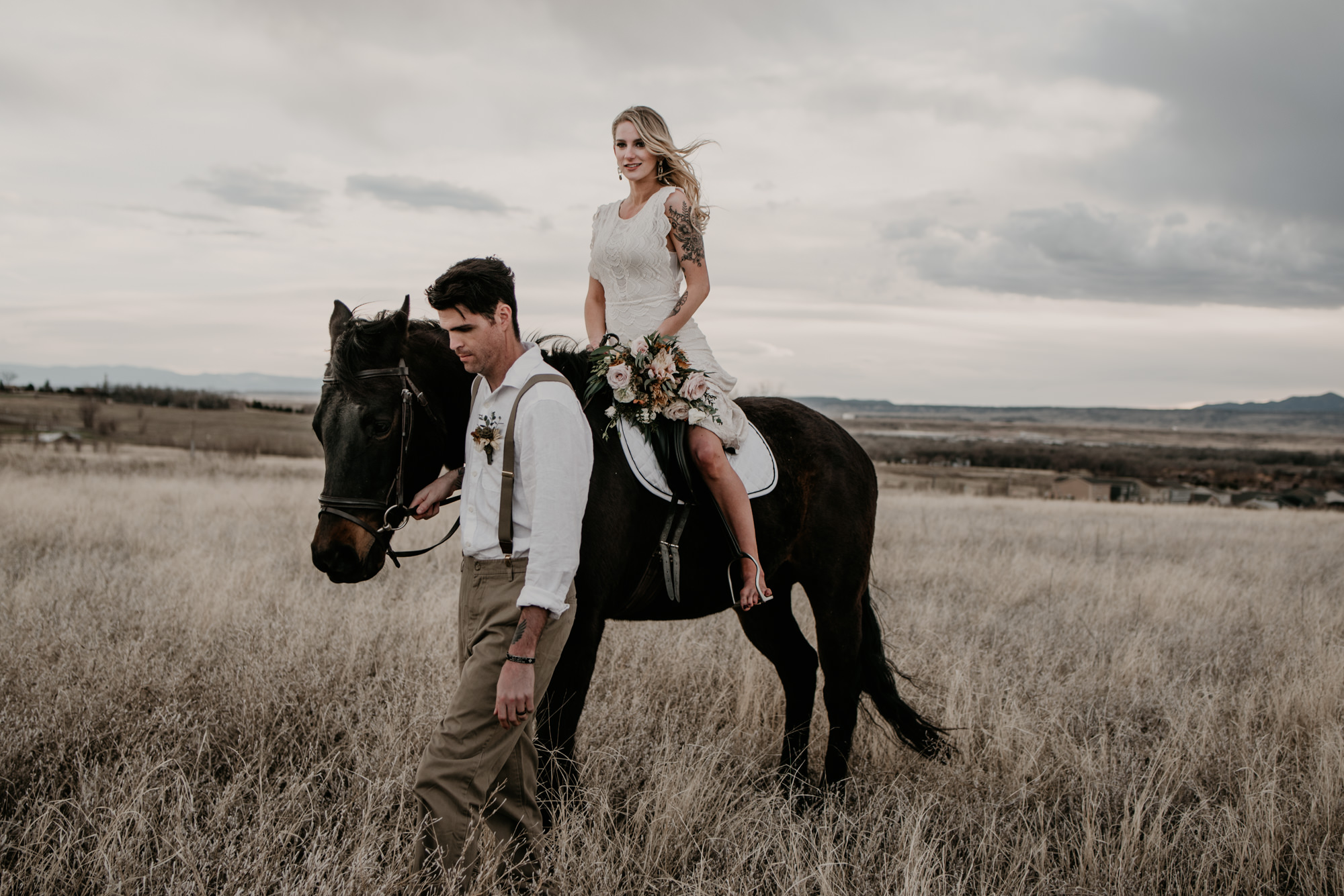 A woman in a white wedding dress rides a black horse led by the groom.