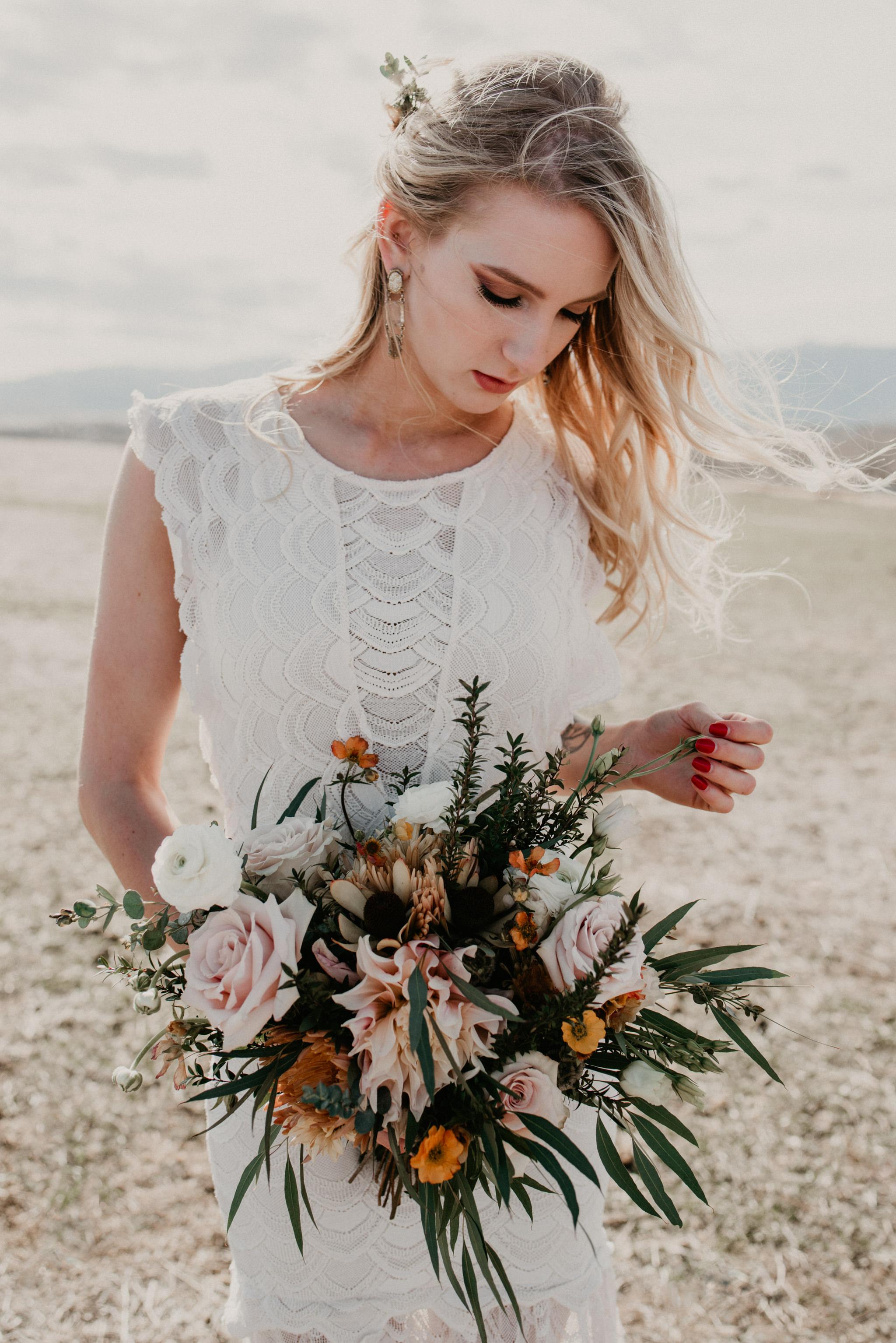 A bride shows off her boho bouquet.