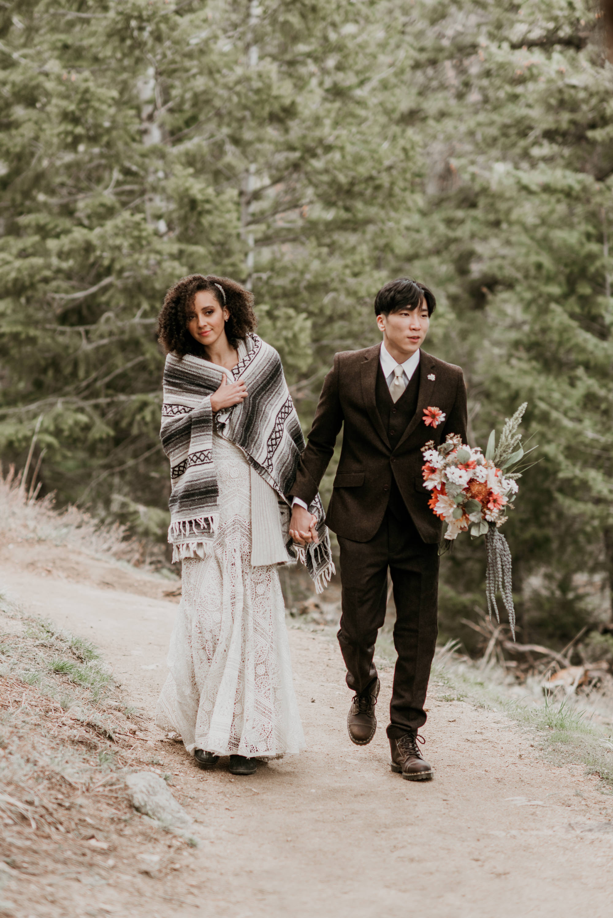 Bride and groom hike hand in hand to their spring mountain elopement.