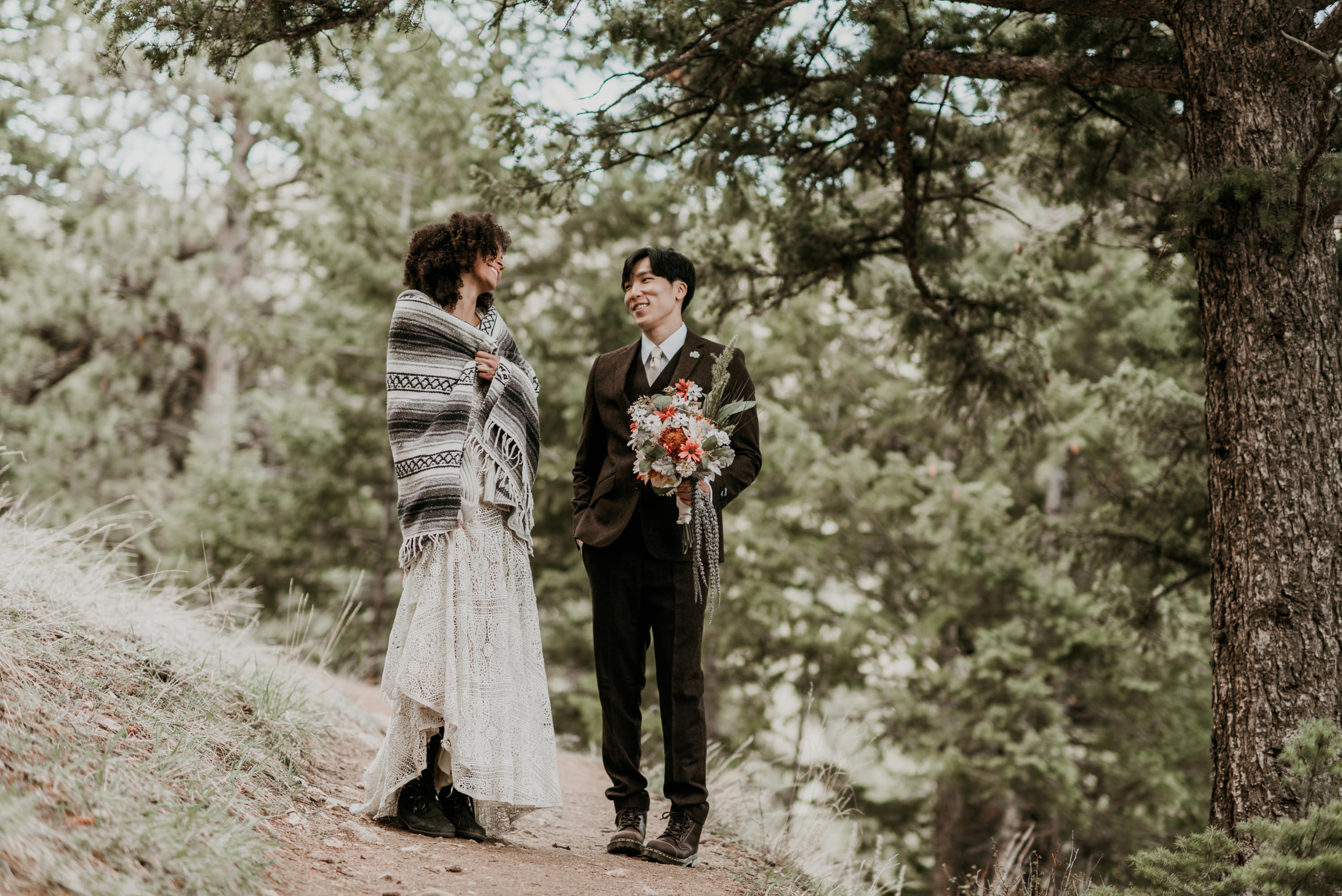 Bride and groom hike hand in hand to their Colorado mountain elopement spot.