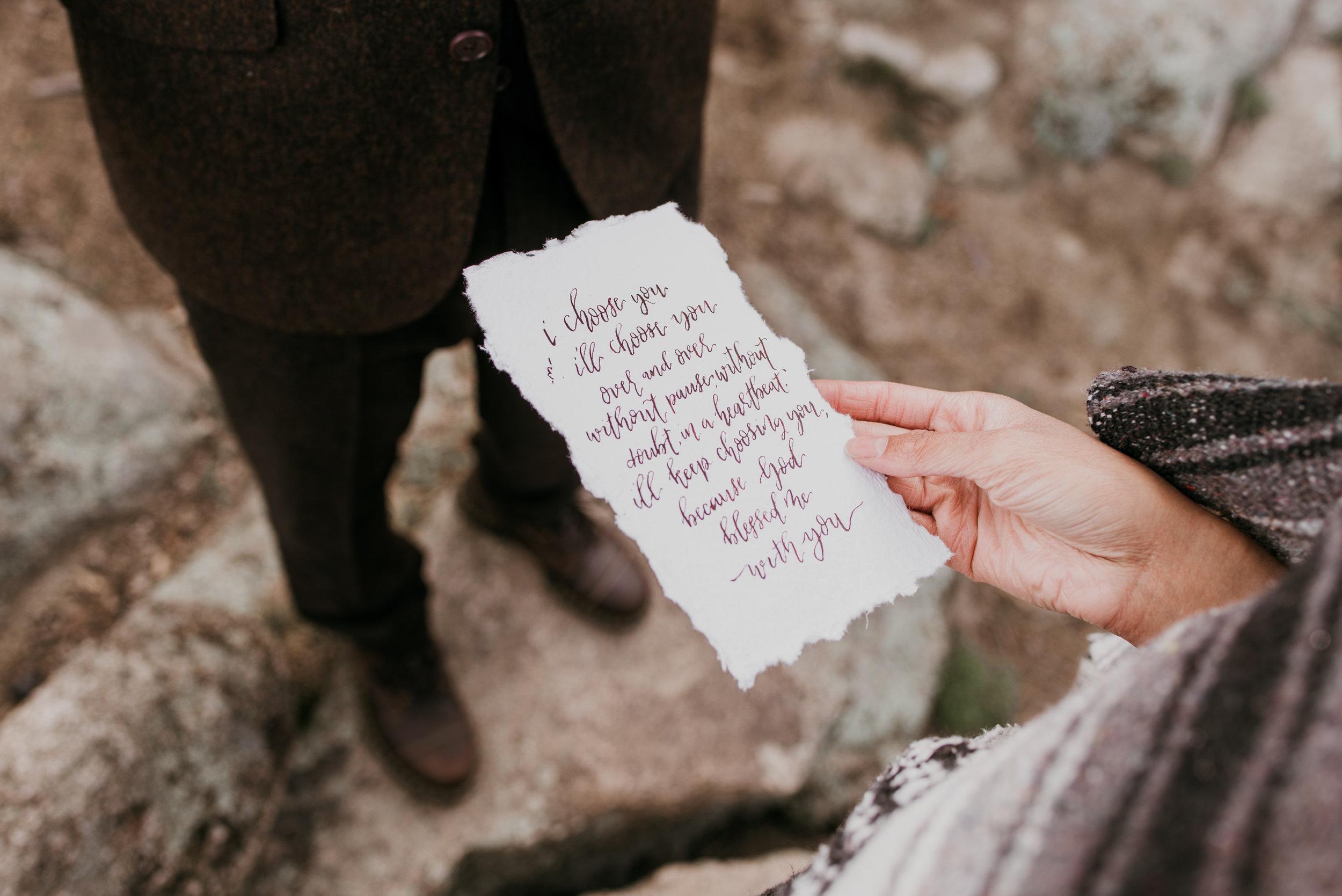 This photo shows handwritten vows in dark red ink, written on torn edge parchment.