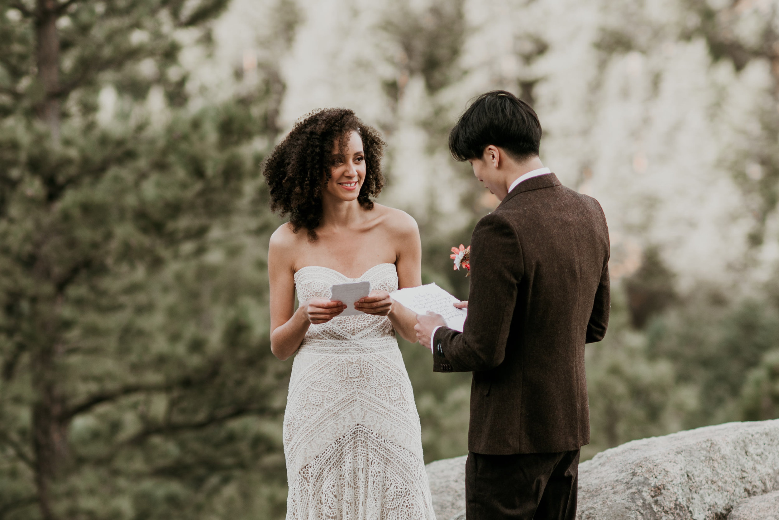 Reading vows on a ledge, the bride is wearing rue de seine and the groom is in a dark brown wool tweed suit.